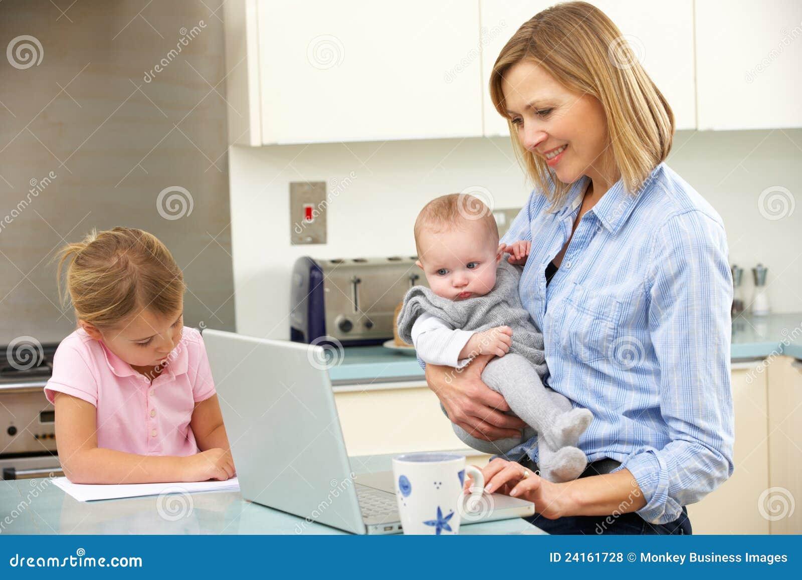 Moeder met kinderen die laptop in keuken met behulp van