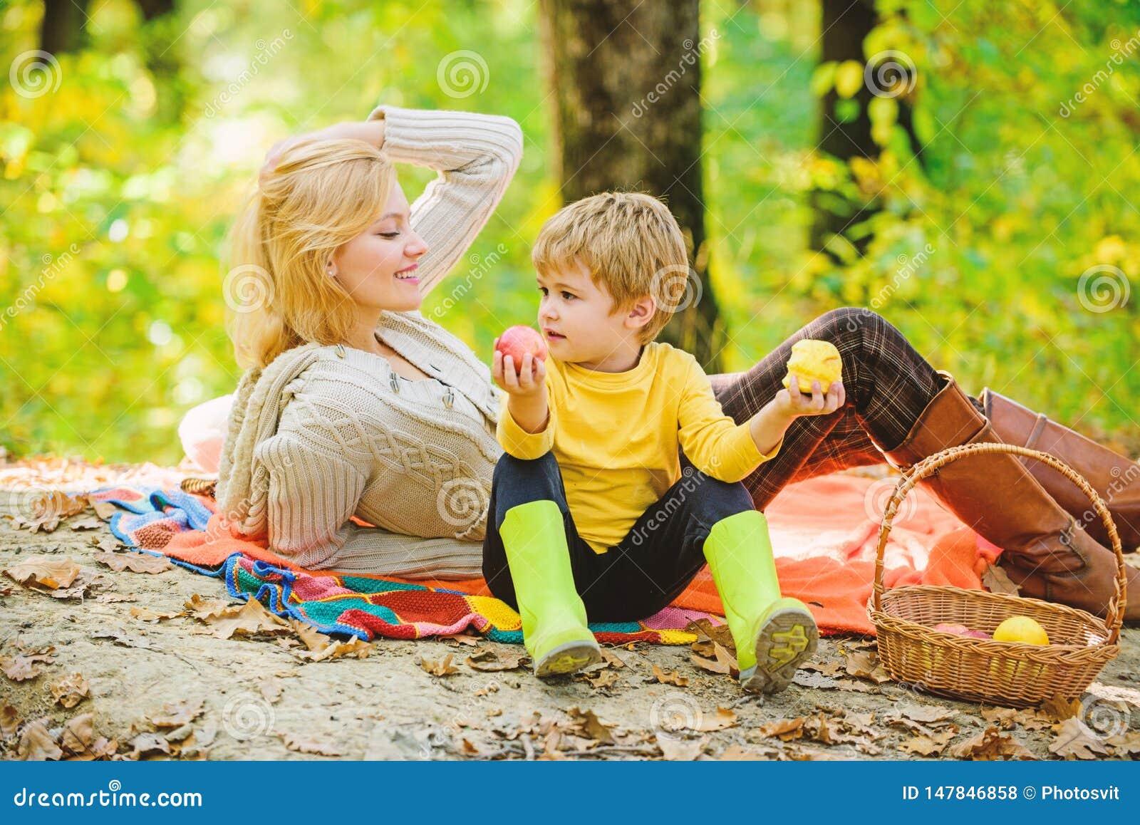 Moeder mooie vrouw en weinig zoon die bospicknick ontspannen Goede dag voor de lentepicknick in aard Het hebben van snack tijdens