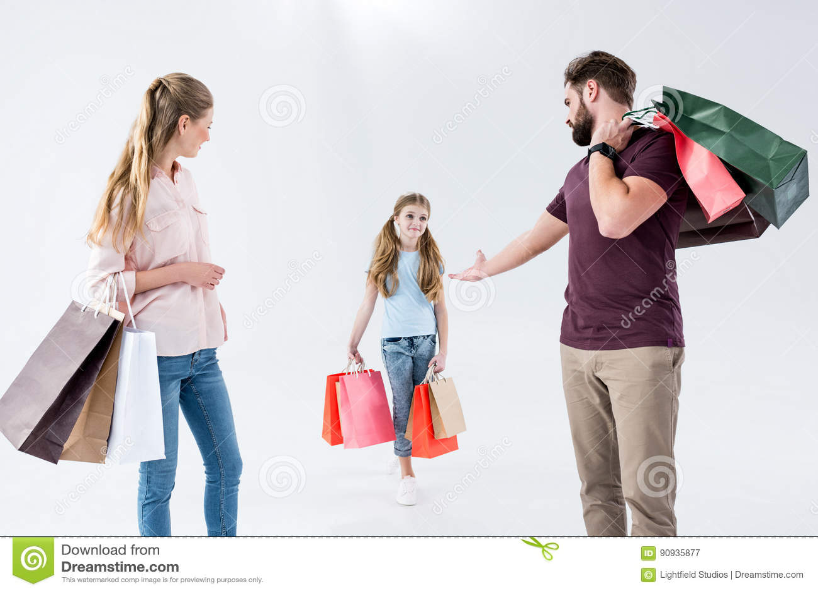 Moeder, vader en dochter die zich met het winkelen zakken bevinden