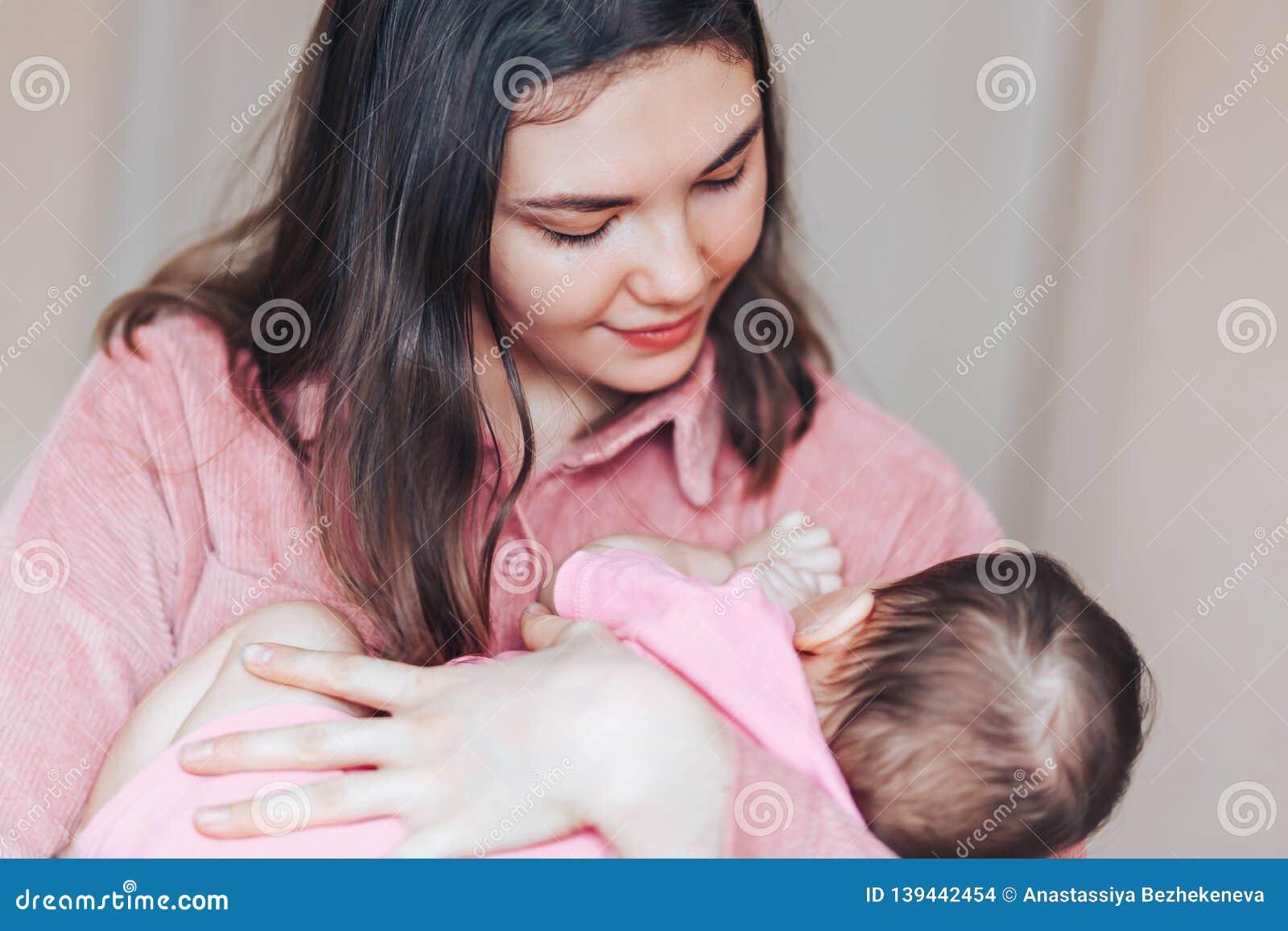 Moederrots haar baby bij handen het glimlachen