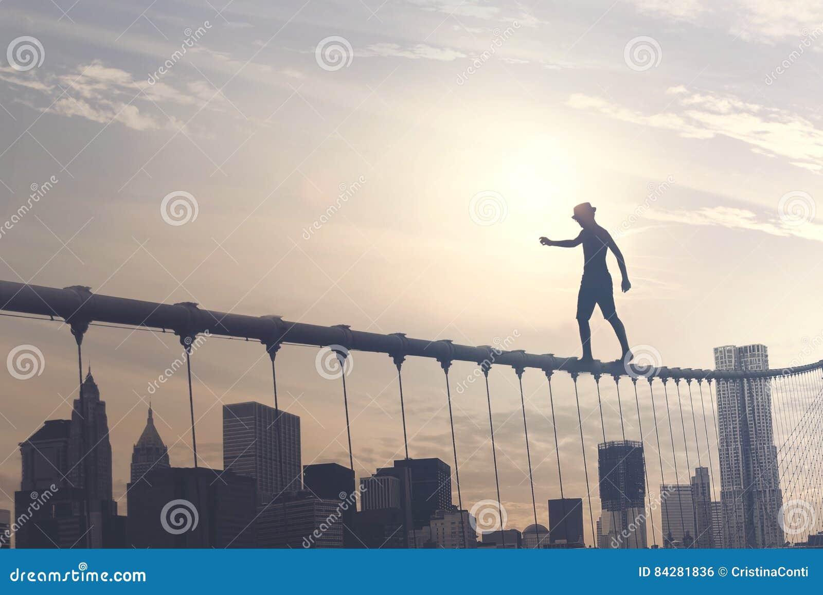 Moedige jongen die op een draad boven de metropool, conceptueel beeld lopen