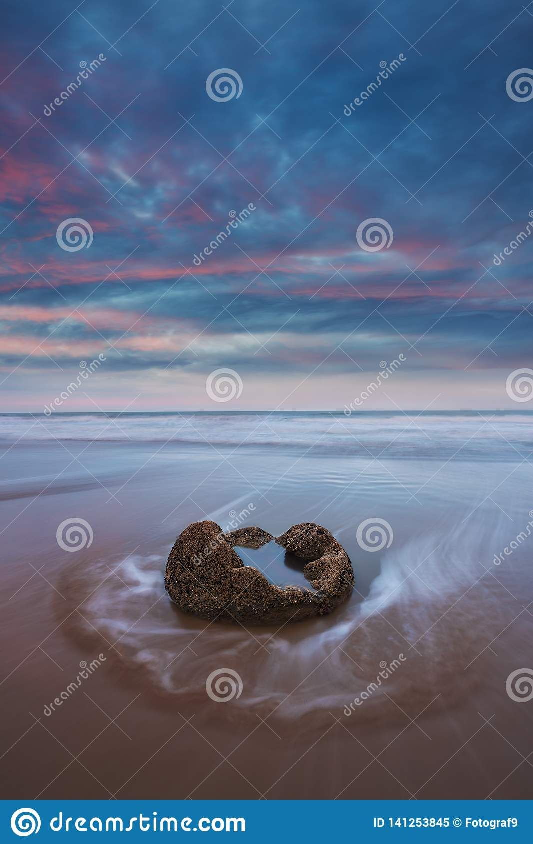 Moeraki Boulders on the Koekohe beach, Eastern coast of New Zealand. Sunset and long exposure and a dramatic dawn sky.