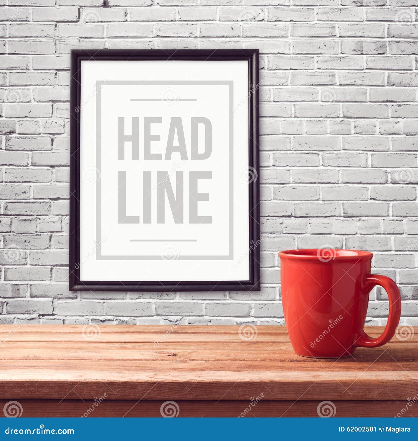 Mofa del cartel encima de la plantilla con la taza roja en la tabla de madera sobre la pared del blanco del ladrillo
