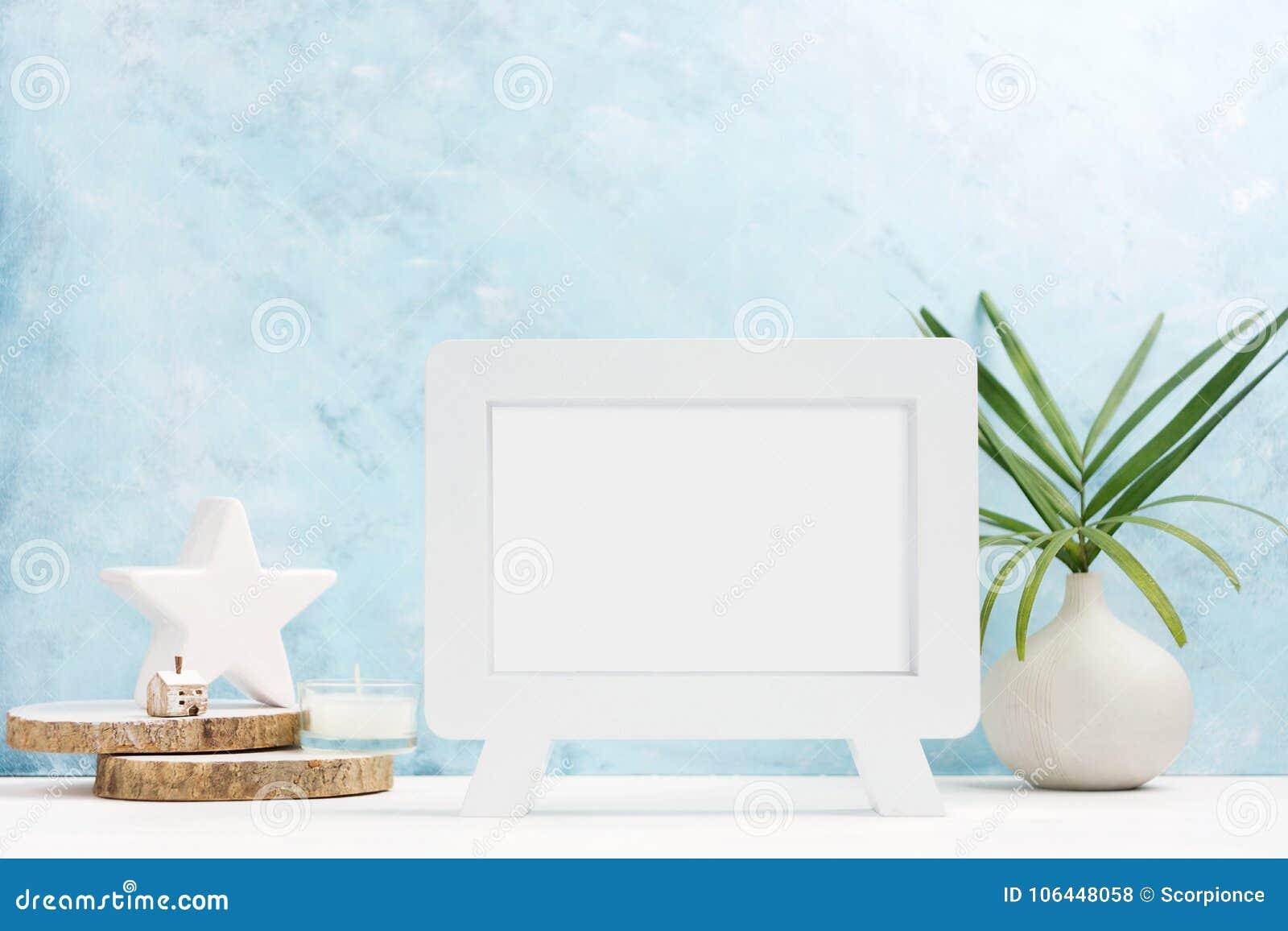 Mofa del marco de la foto de VWhite para arriba con las plantas en el florero, decoración de cerámica en estante en fondo azul Es