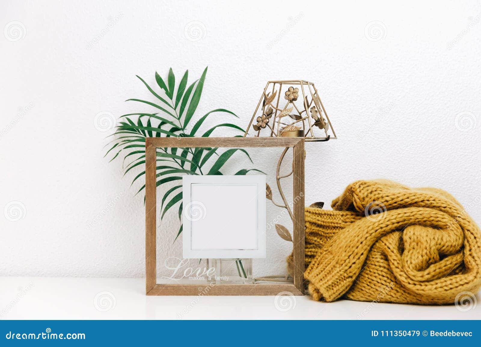 Mofa mínima encima del marco de madera con las hojas tropicales verdes y el suéter caliente de moda