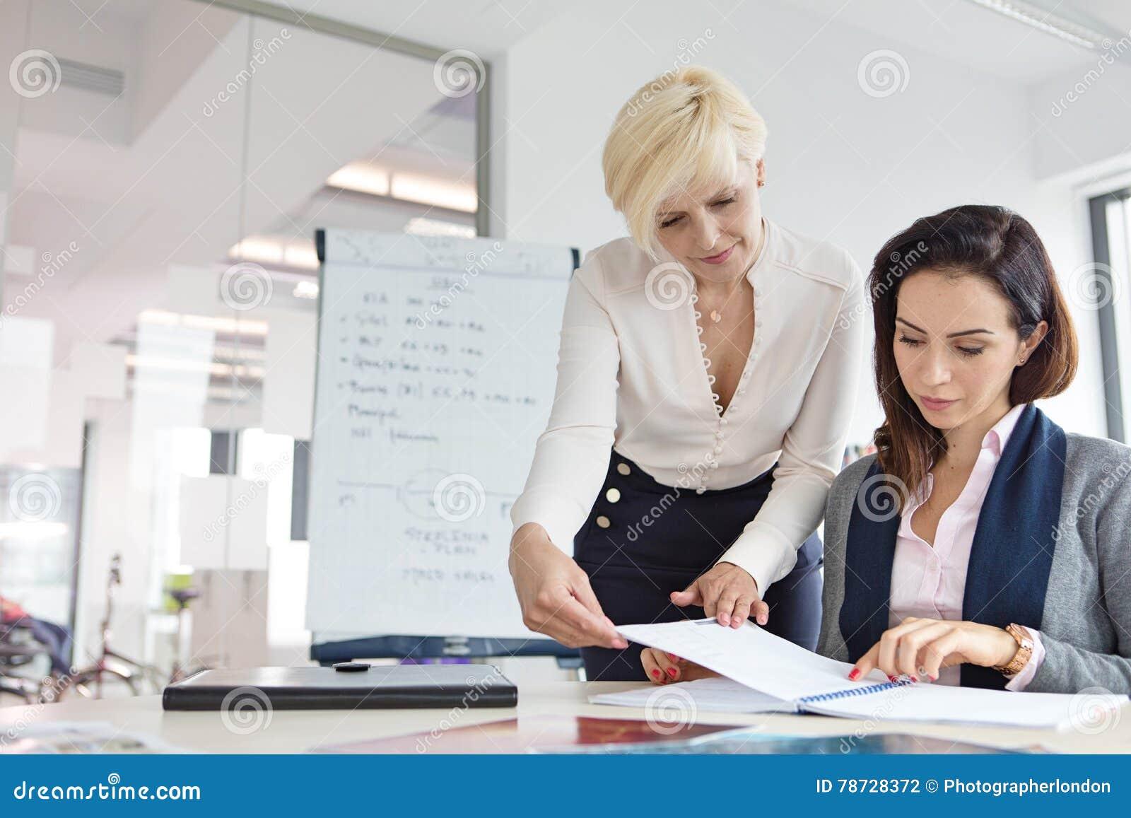 Mogen affärskvinna med den kvinnliga kollegan som i regeringsställning granskar projekt på skrivbordet