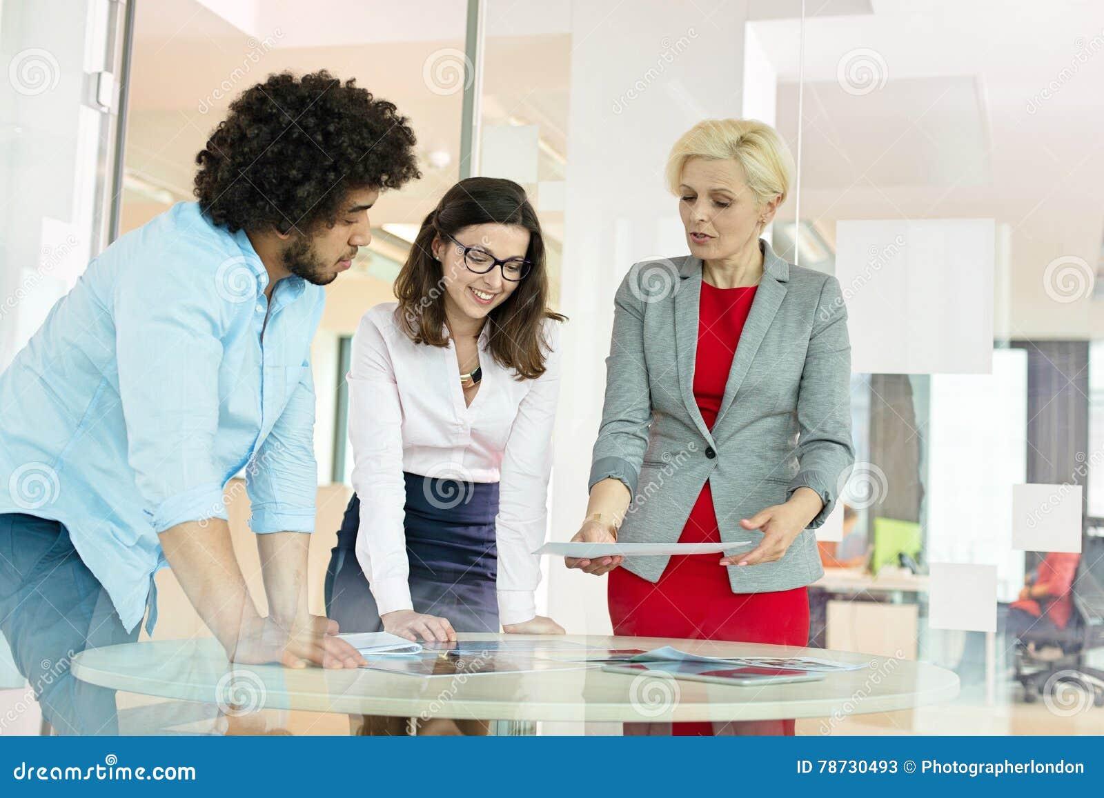 Mogen affärskvinna med kollegor som i regeringsställning diskuterar över projekt på tabellen