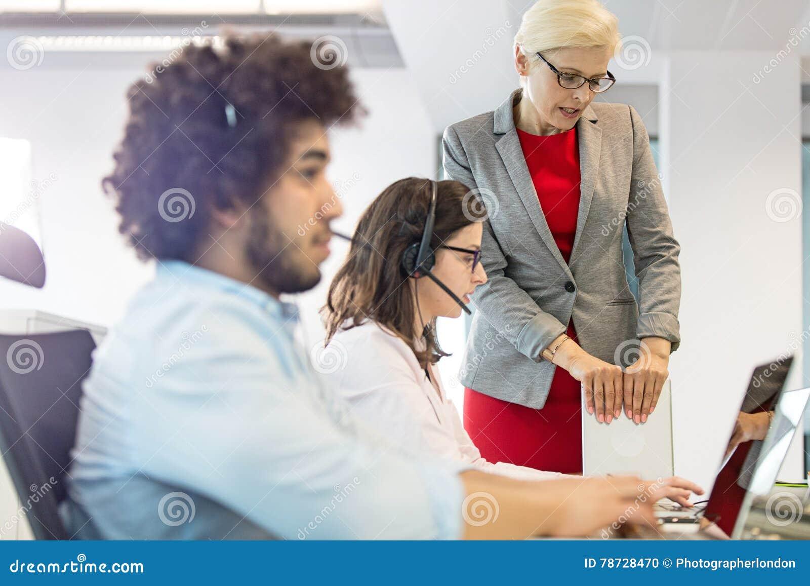 Mogen affärskvinna som hjälper den kvinnliga operatören med kollegan i förgrund på kontoret