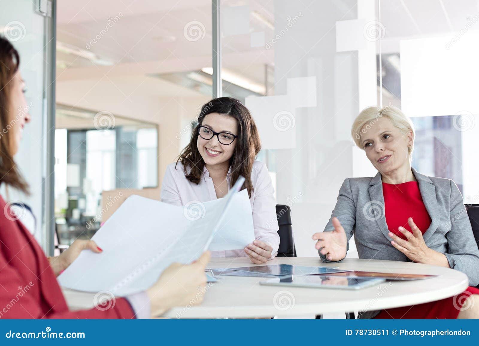 Mogen affärskvinna som i regeringsställning diskuterar med kvinnliga kollegor på tabellen