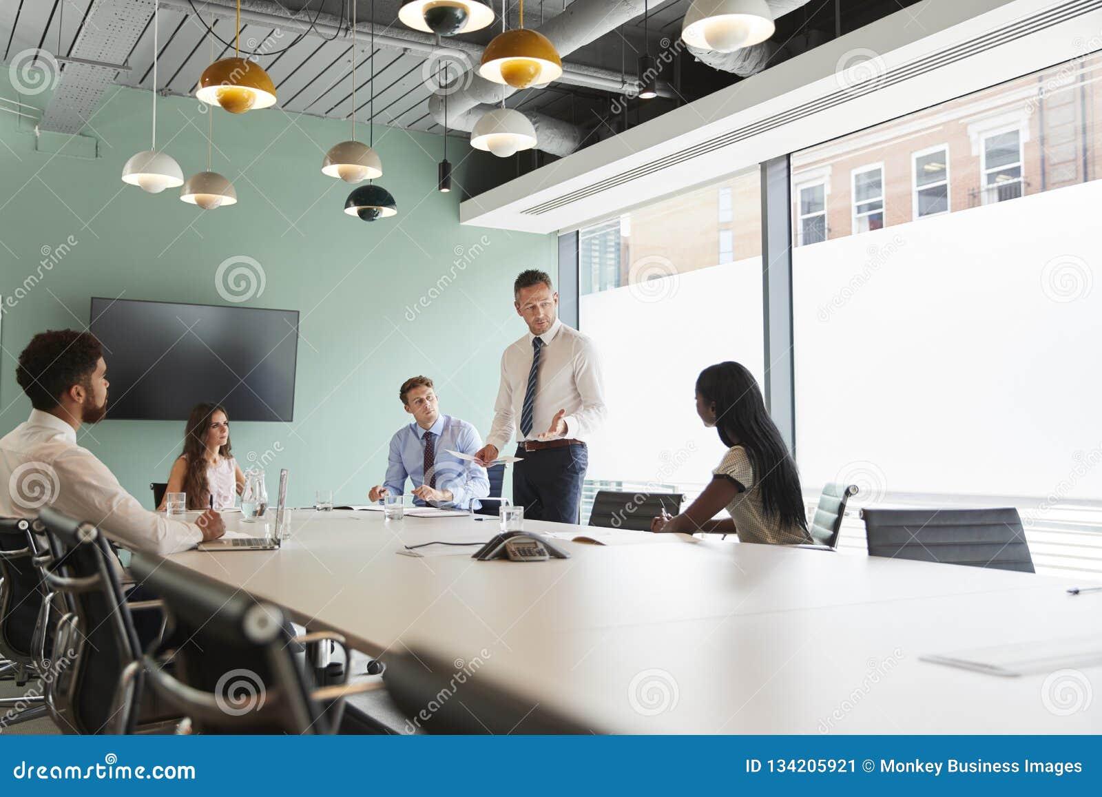 Mogen affärsman Giving Boardroom Presentation till kollegor i mötesrum