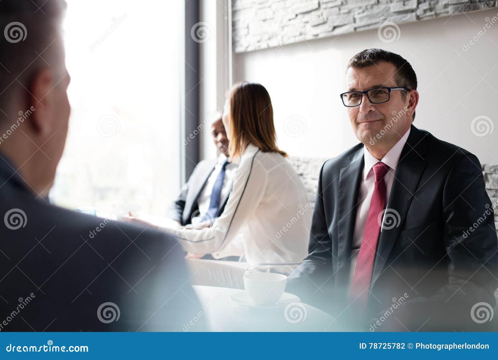 Mogen affärsman med kafeterian för kollegor i regeringsställning