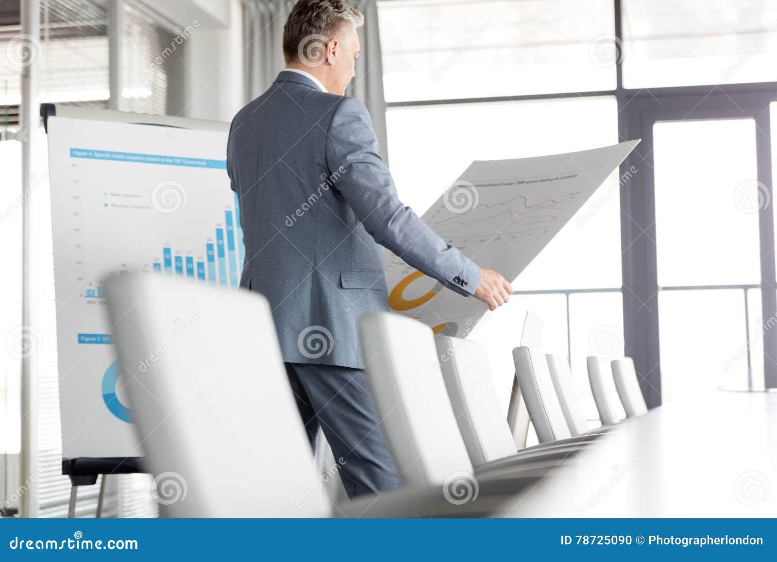 Mogen affärsman som analyserar grafen på diagram i bräderum