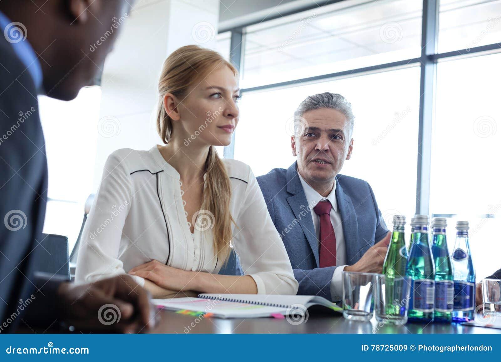 Mogen affärsman som diskuterar med kollegor på tabellen i bräderum