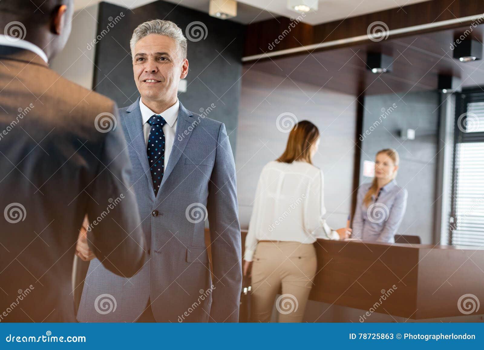 Mogen affärsman som i regeringsställning skakar händer med manliga kollegor