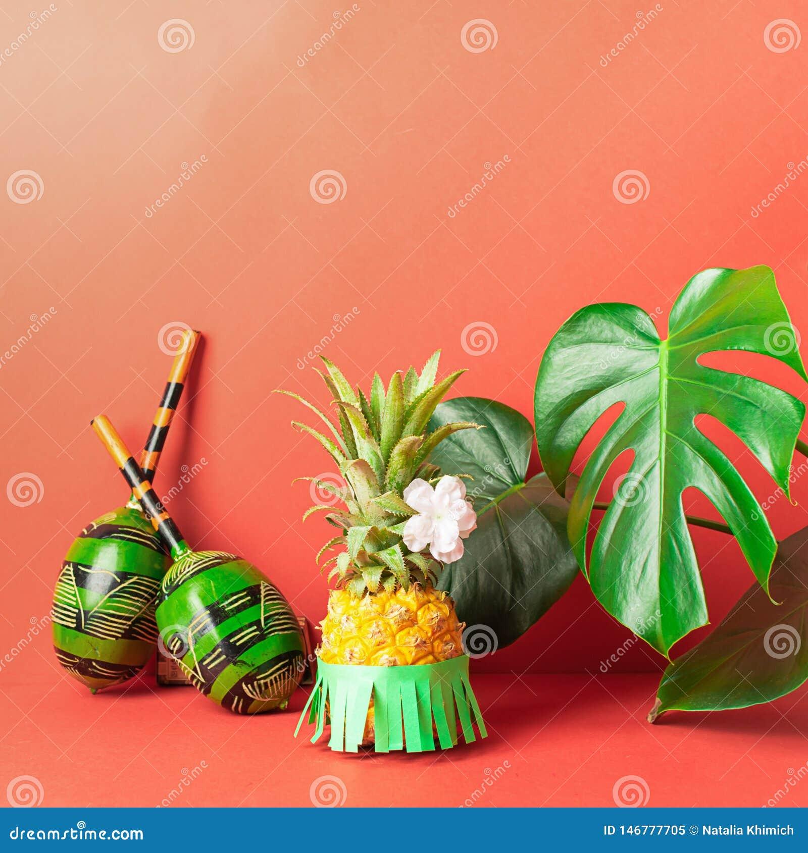 Mogen ananas i gröna maracas för en kjol på en röd bakgrund Rekreation- och partibegrepp Horisontal inrama
