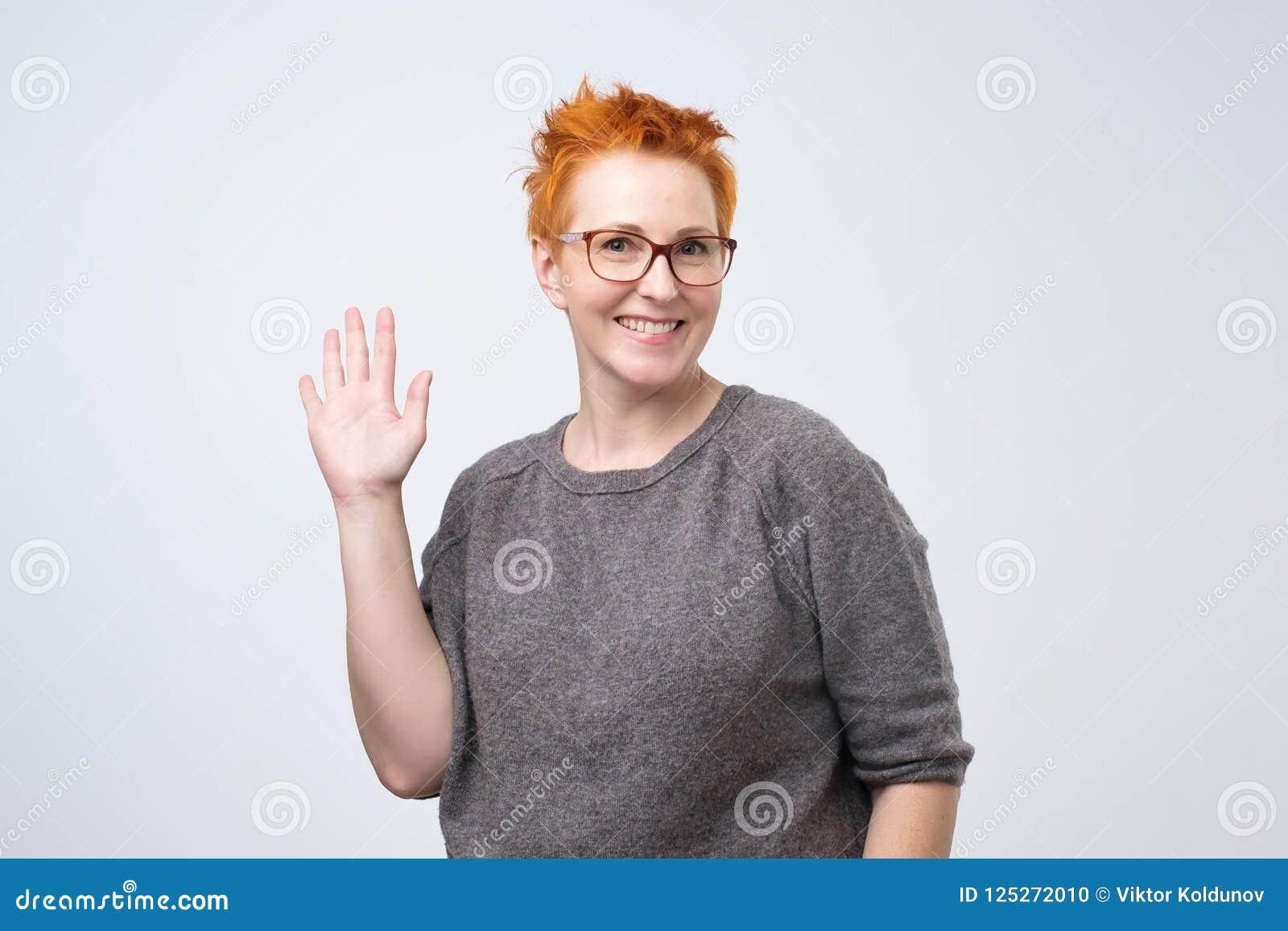 Mogen caucasian kvinna för realitet med den röda frisyren och exponeringsglas som ler den vänliga och vinkande handen på kameran