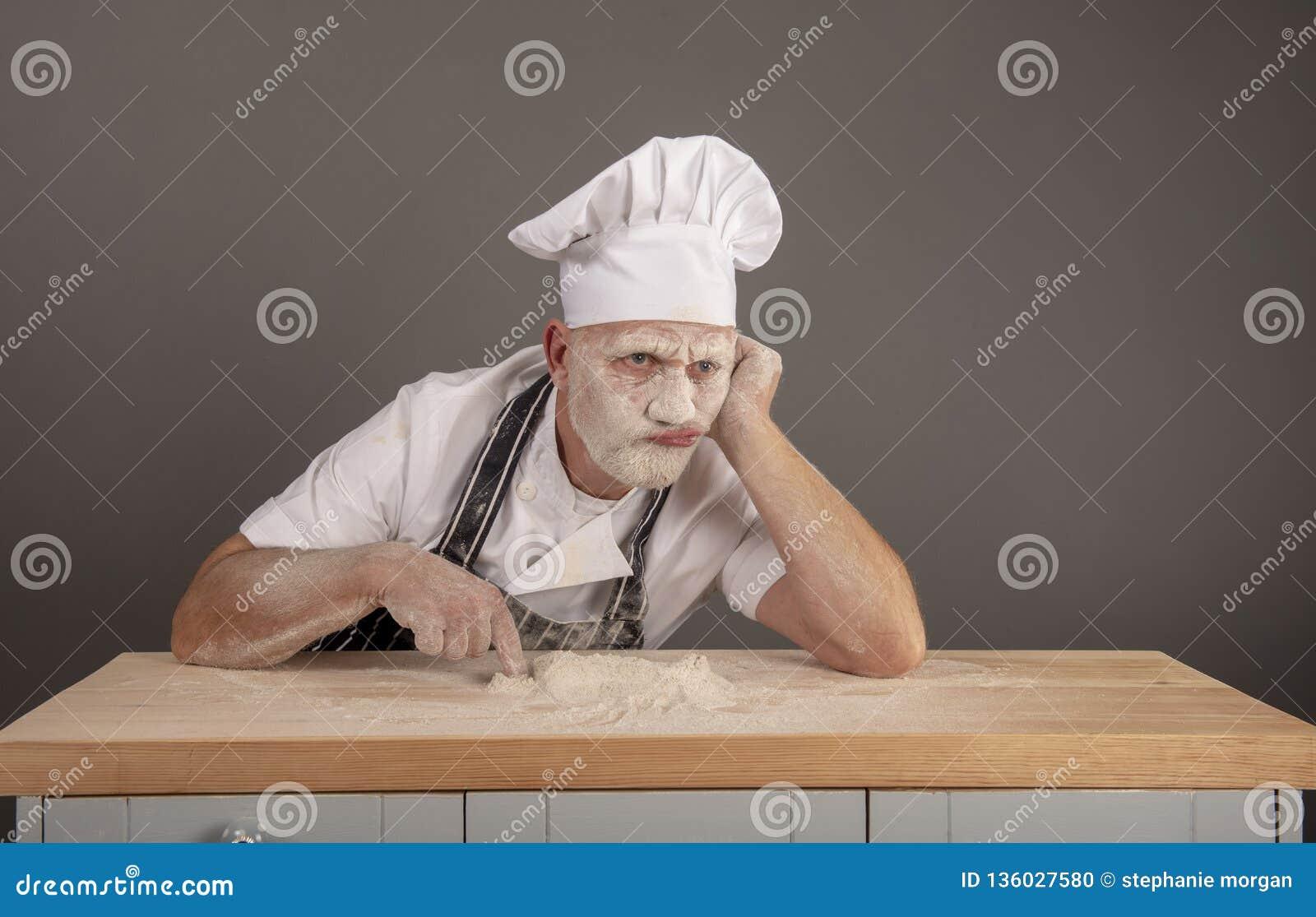 Mogen kock som täckas i mjöl som ser förargat och matat upp