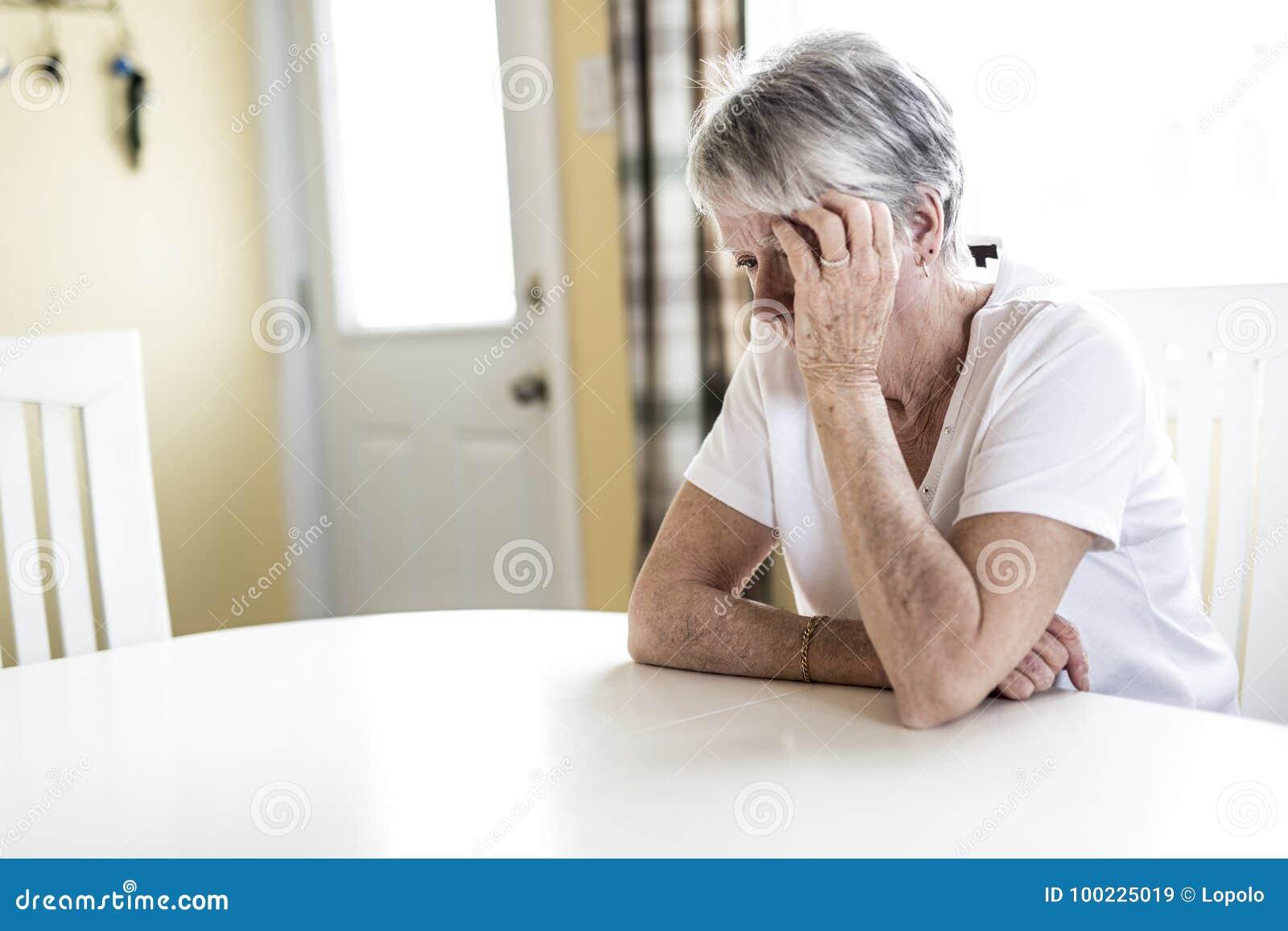Mogen kvinna hemma som trycker på hennes huvud med henne händer, medan ha en huvudvärk smärta