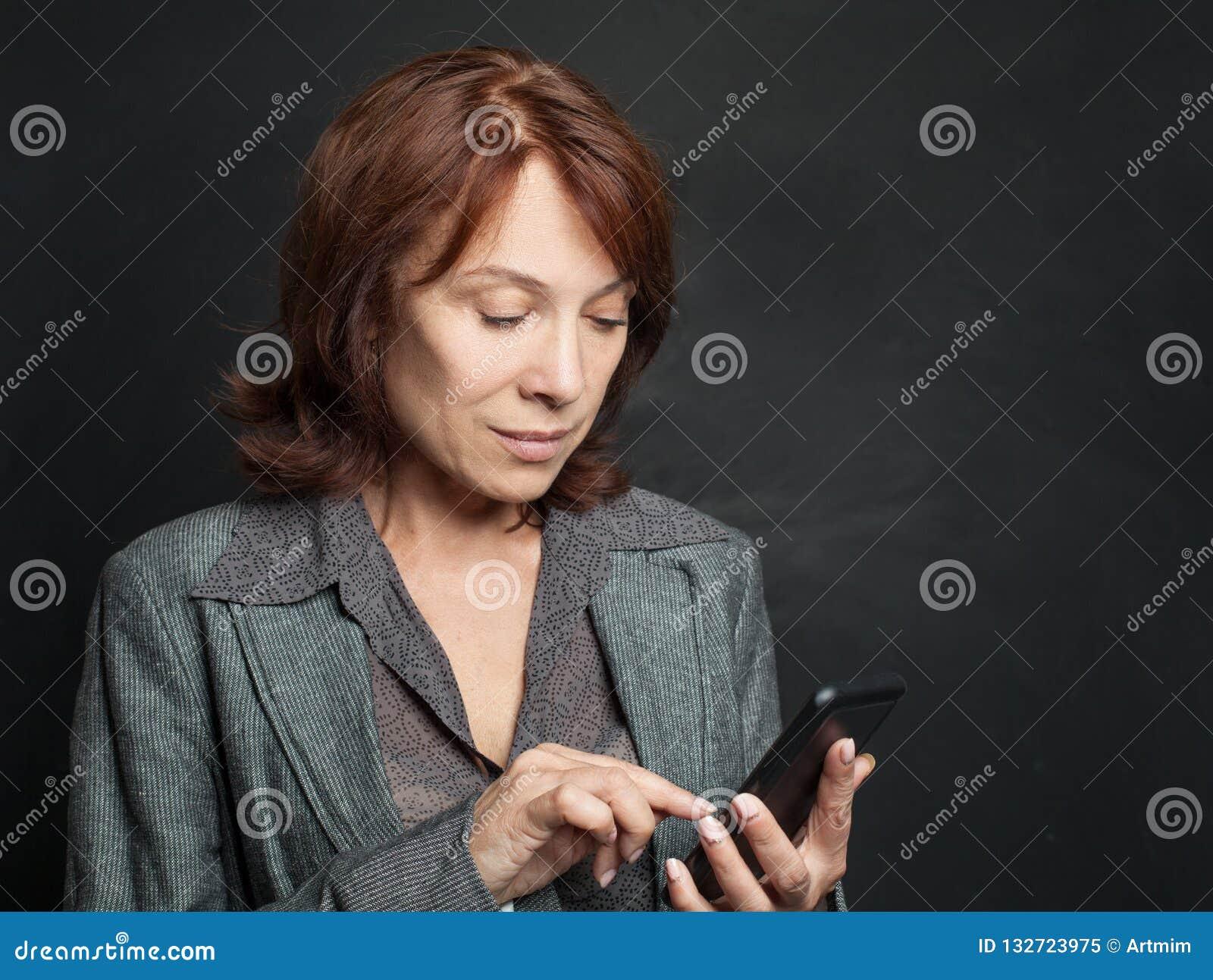 Mogen kvinna med att prata för smartphone