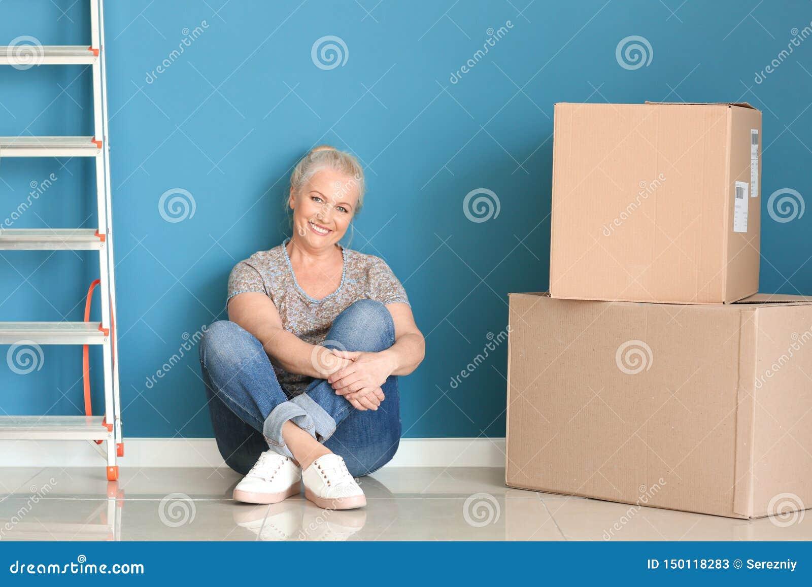 Mogen kvinna med flyttningaskar som sitter på golv på det nya hemmet