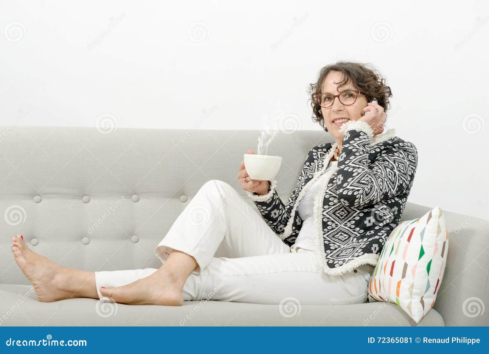 Mogen kvinna med telefonen som dricker te