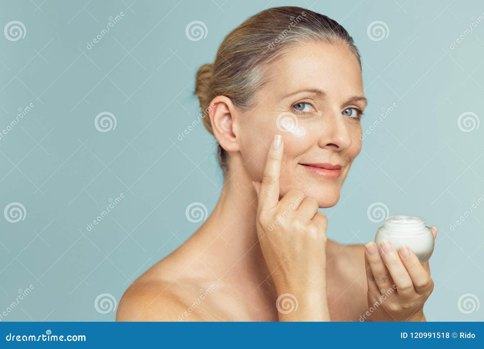Mogen kvinna som applicerar hudkräm på framsida