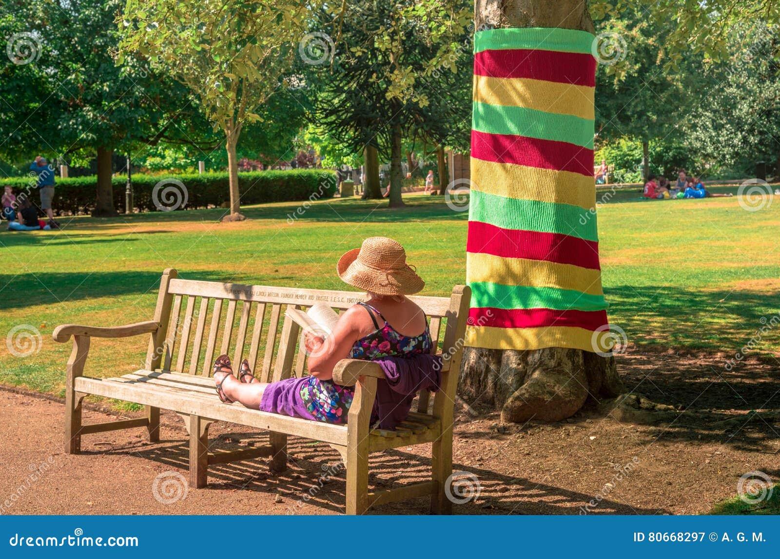 Mogen kvinna som kopplar av i en solig dag i en parkera av UK