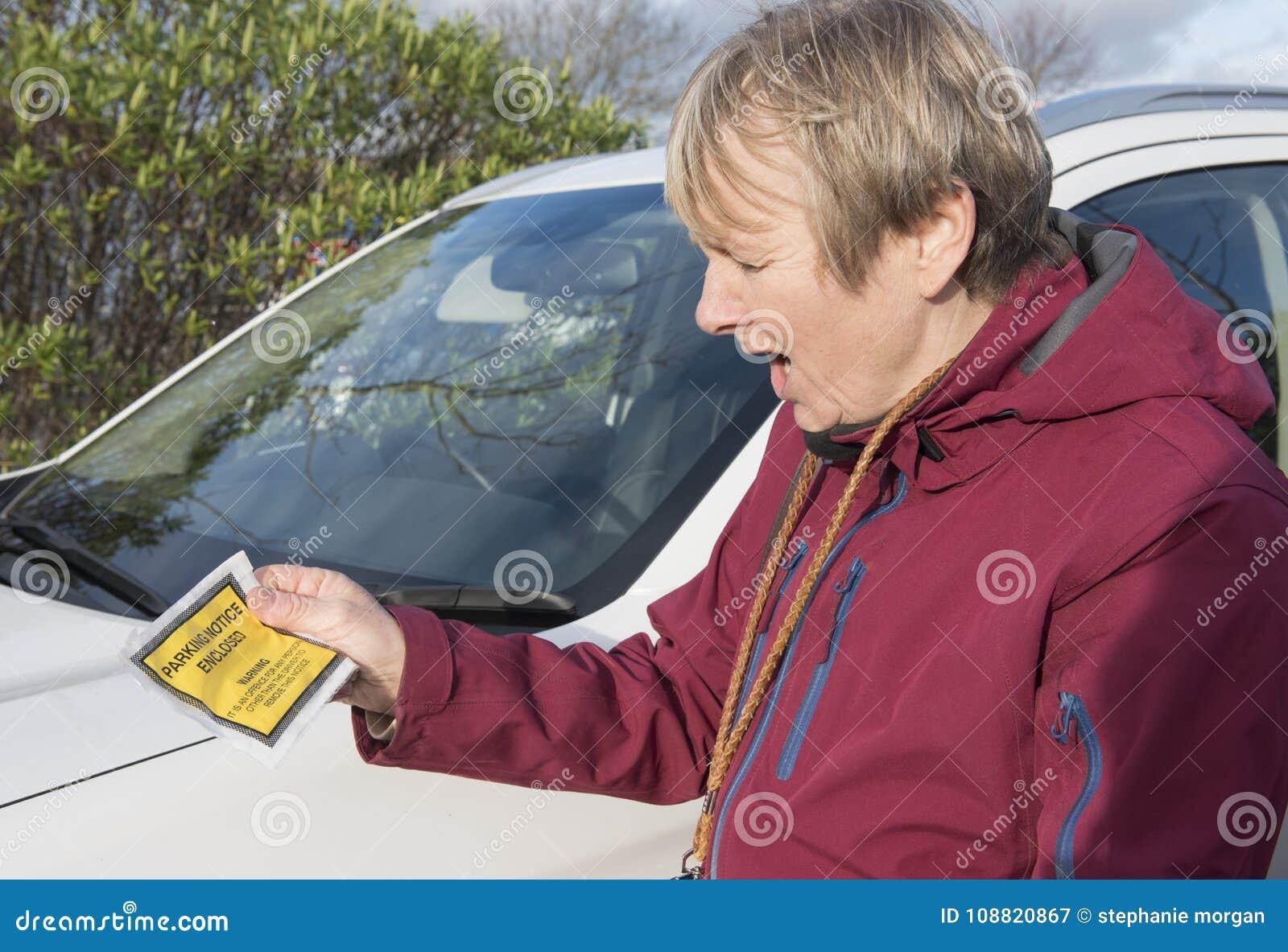 Mogen kvinna som rymmer en parkeringsbiljett