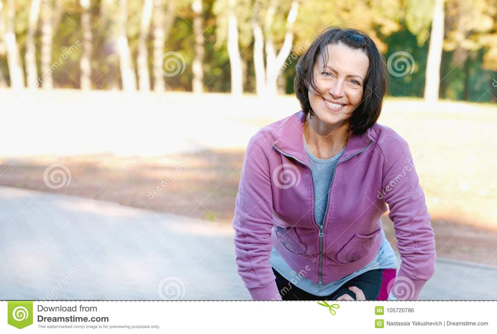Mogen kvinnalöpare som tar en vila, når att ha kört i parkera