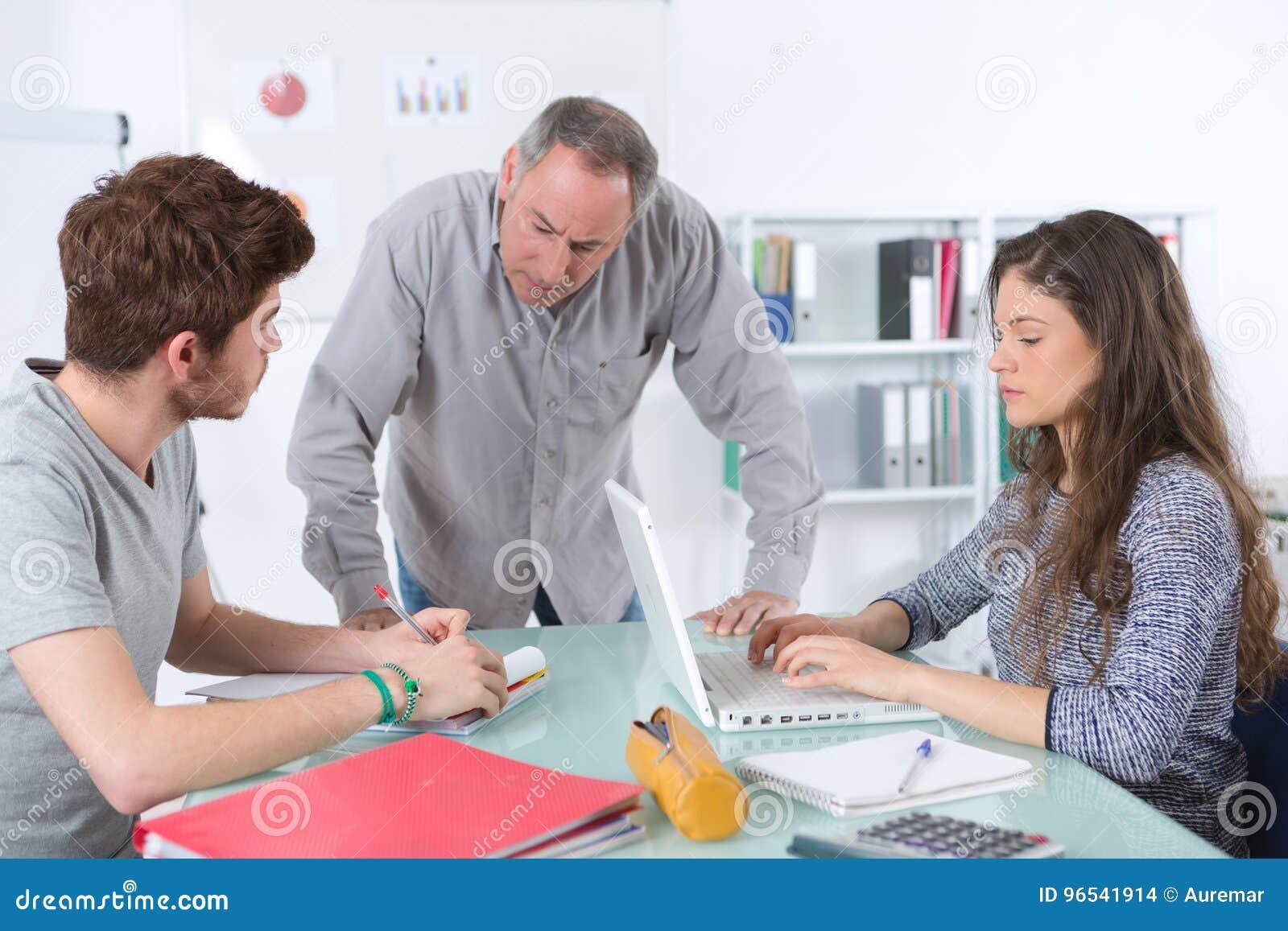 Mogen lärare och tonåriga studenter i klassrum