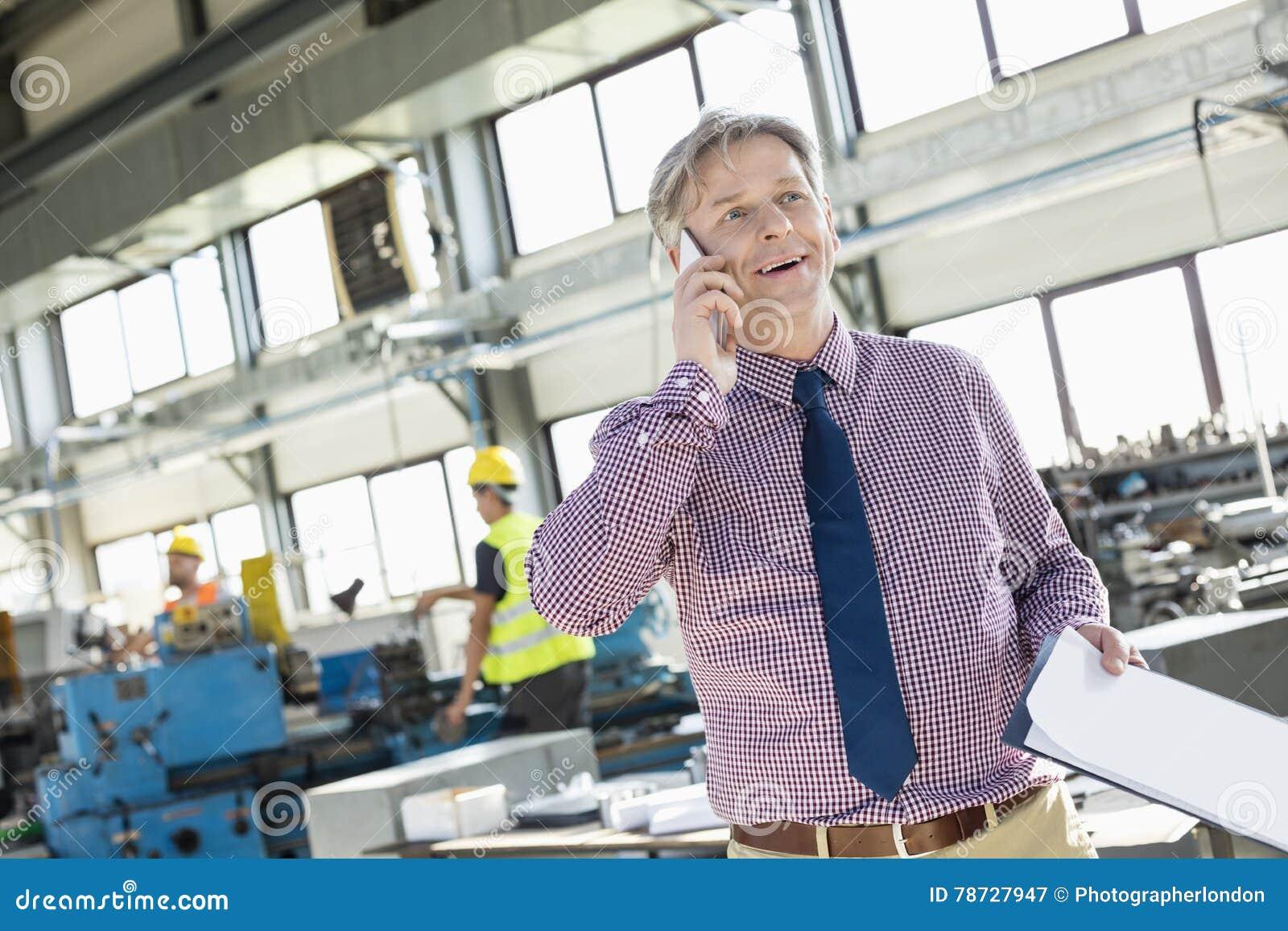 Mogen manlig arbetsledare med skrivplattan som talar på mobiltelefonen i bransch