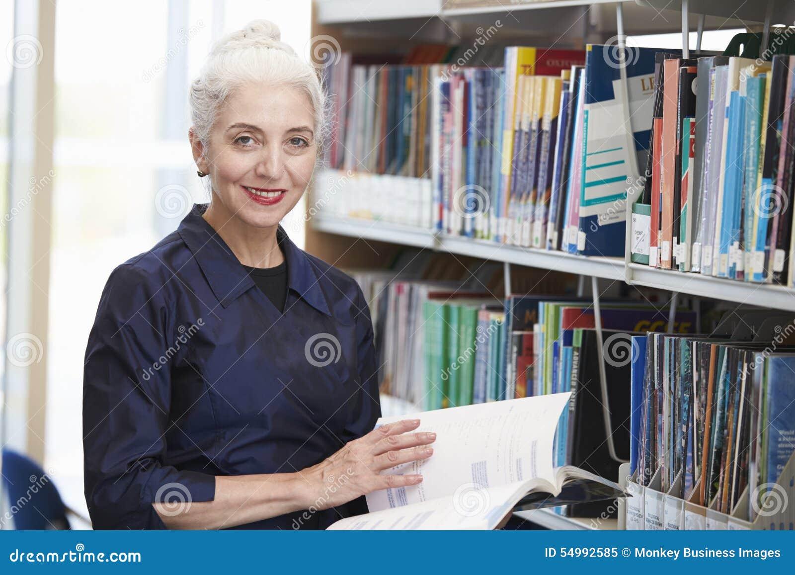 Mogen student Studying In Library för kvinnlig