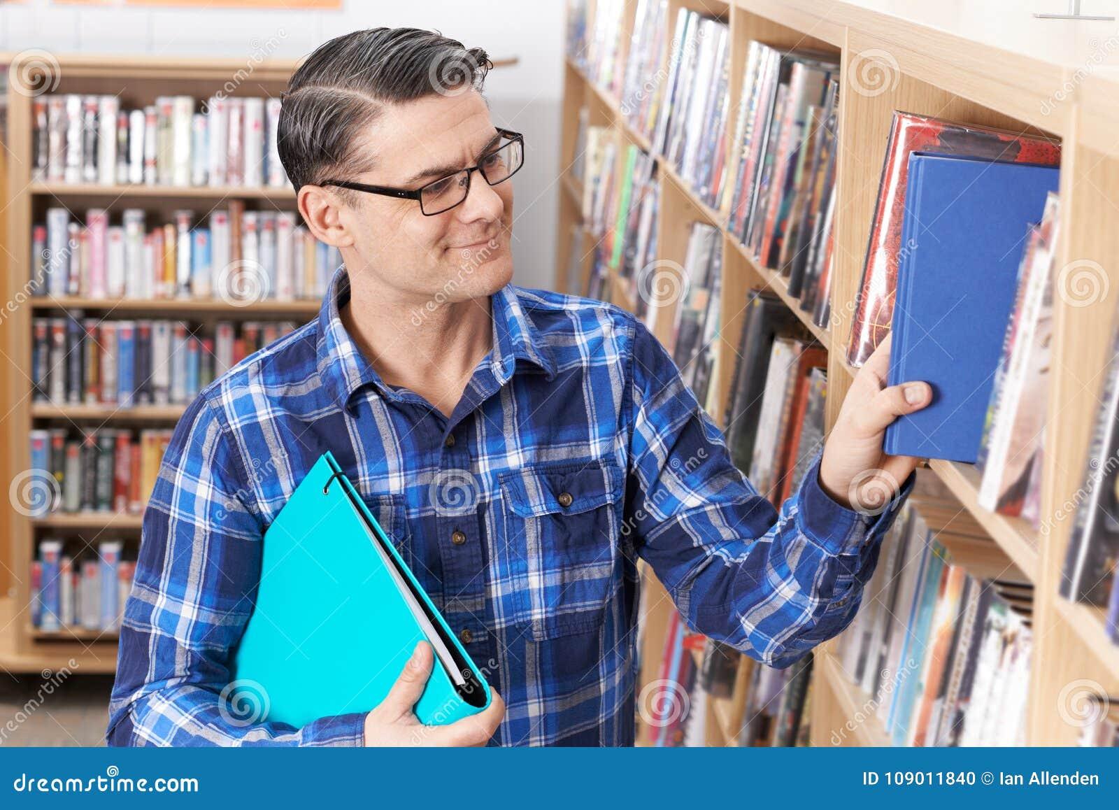 Mogen Taking Book From för manlig student hylla i arkiv
