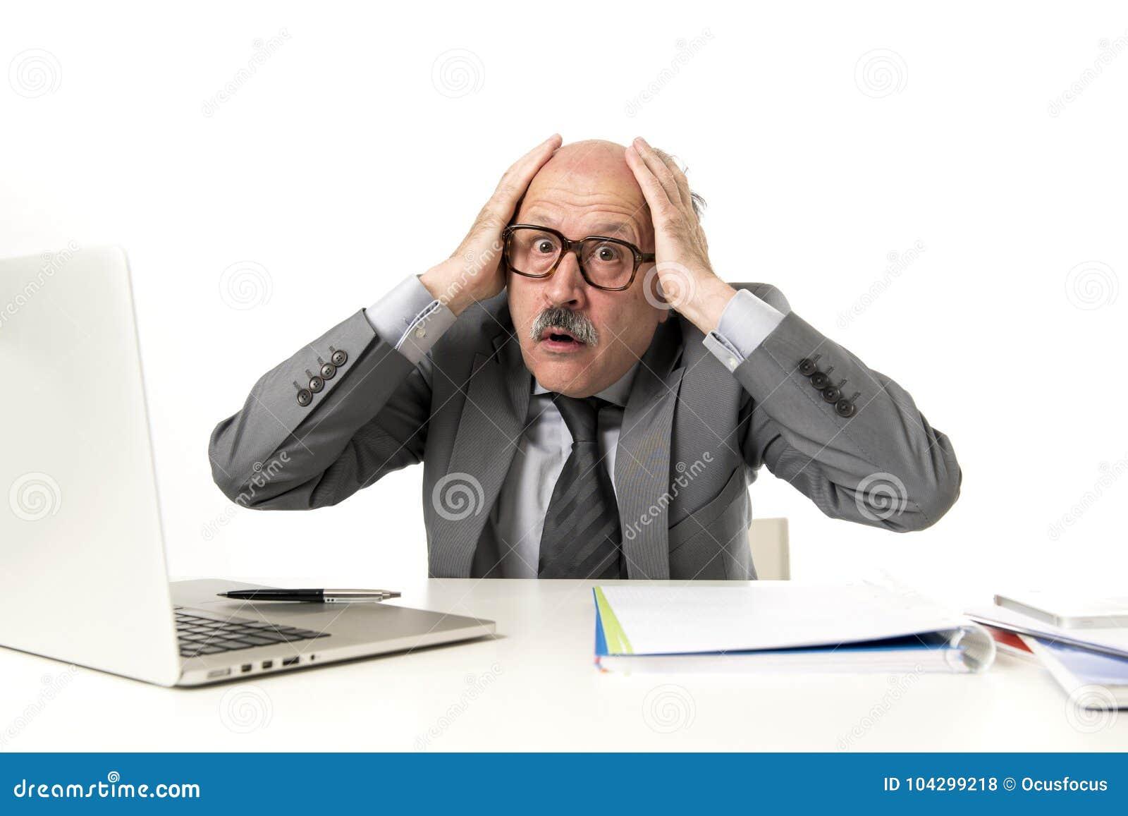 Mogen upptagen affärsman för pensionär med flinten på hans funktionsdugliga stressat för 60-tal och frustrerat på skrivbordet för