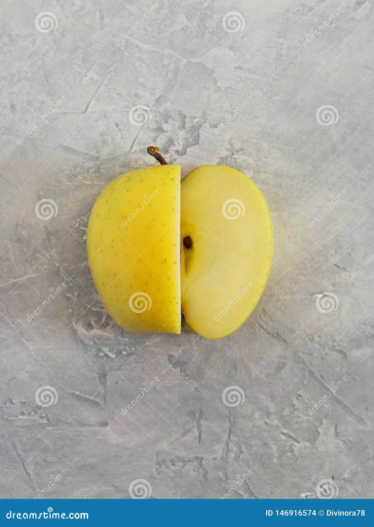 Moget gult äpple på en grå konkret bakgrund