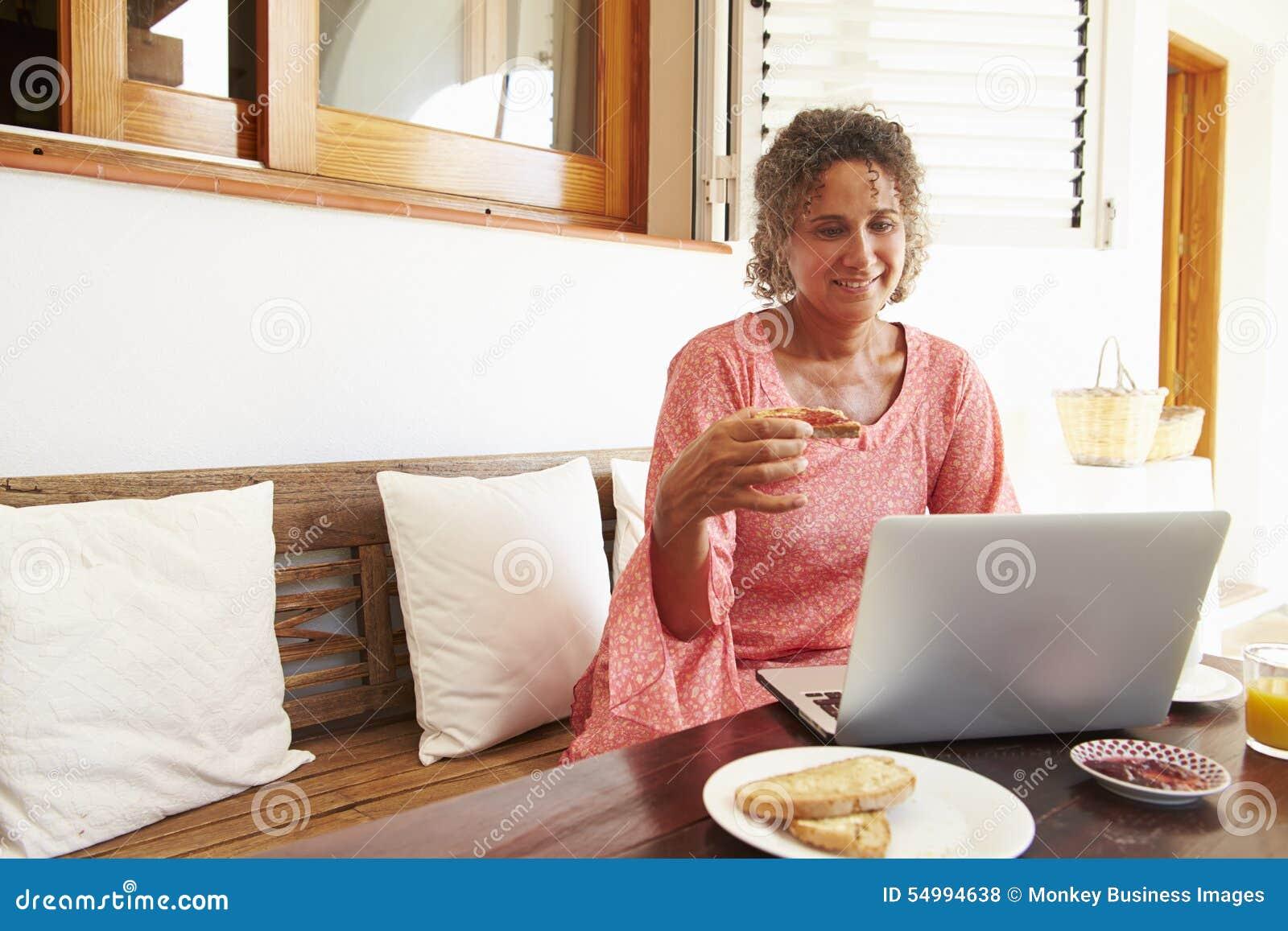 Moget kvinnasammanträde på frukosttabellen genom att använda bärbara datorn