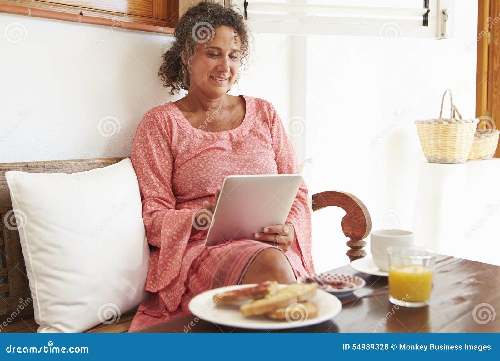 Moget kvinnasammanträde på frukosttabellen genom att använda den Digital minnestavlan