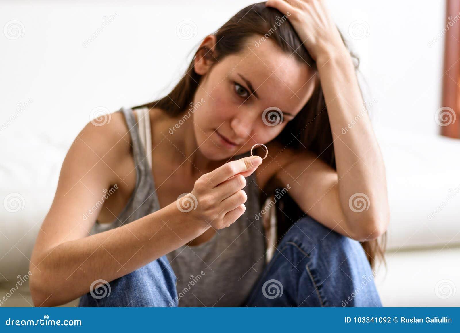 Moglie arrabbiata ed offensiva deprimente dopo il divorzio, tenente con la mano una fede nuziale che si siede su un pavimento del