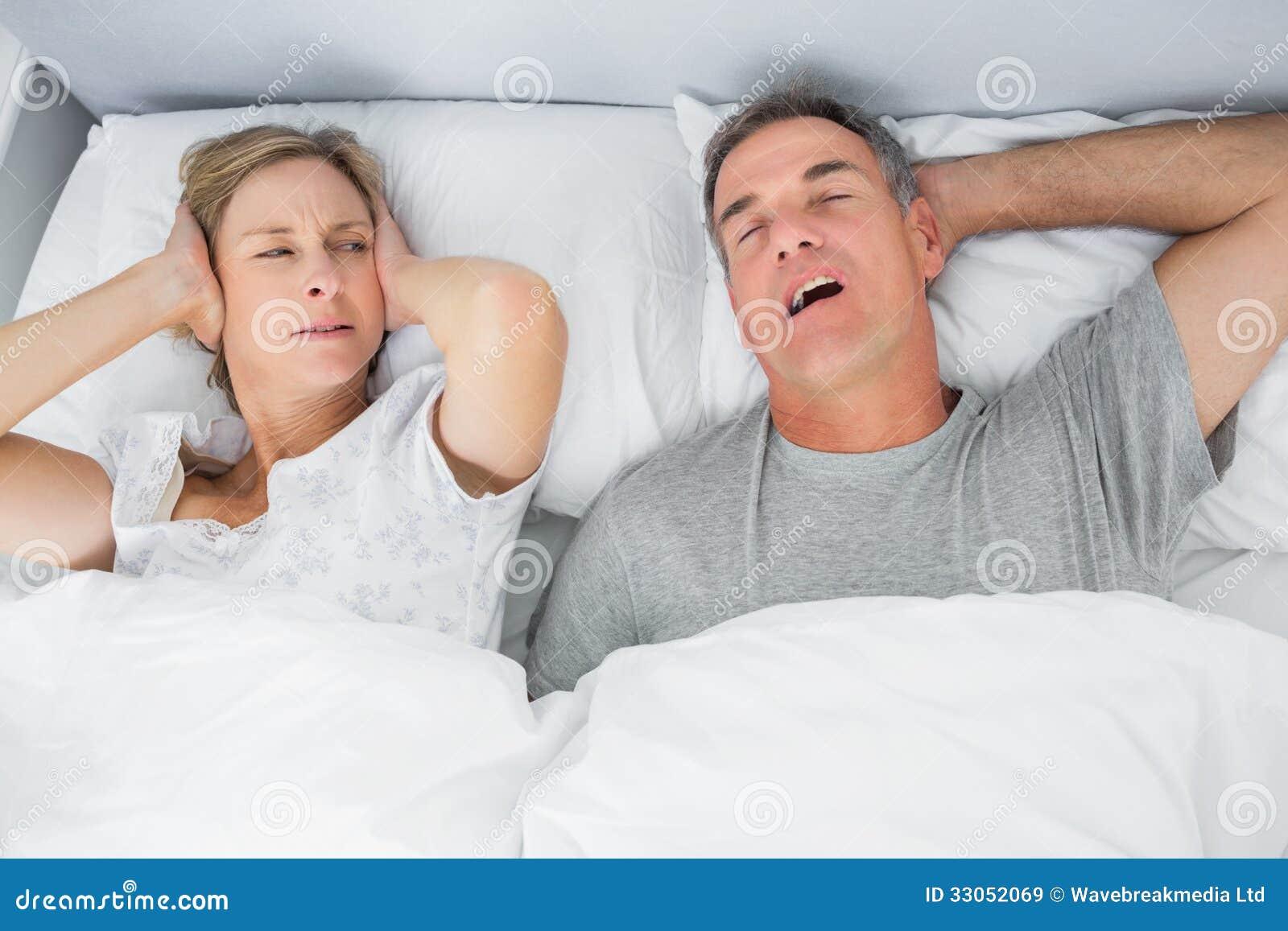 Moglie infastidita che blocca le sue orecchie da rumore del marito che russa