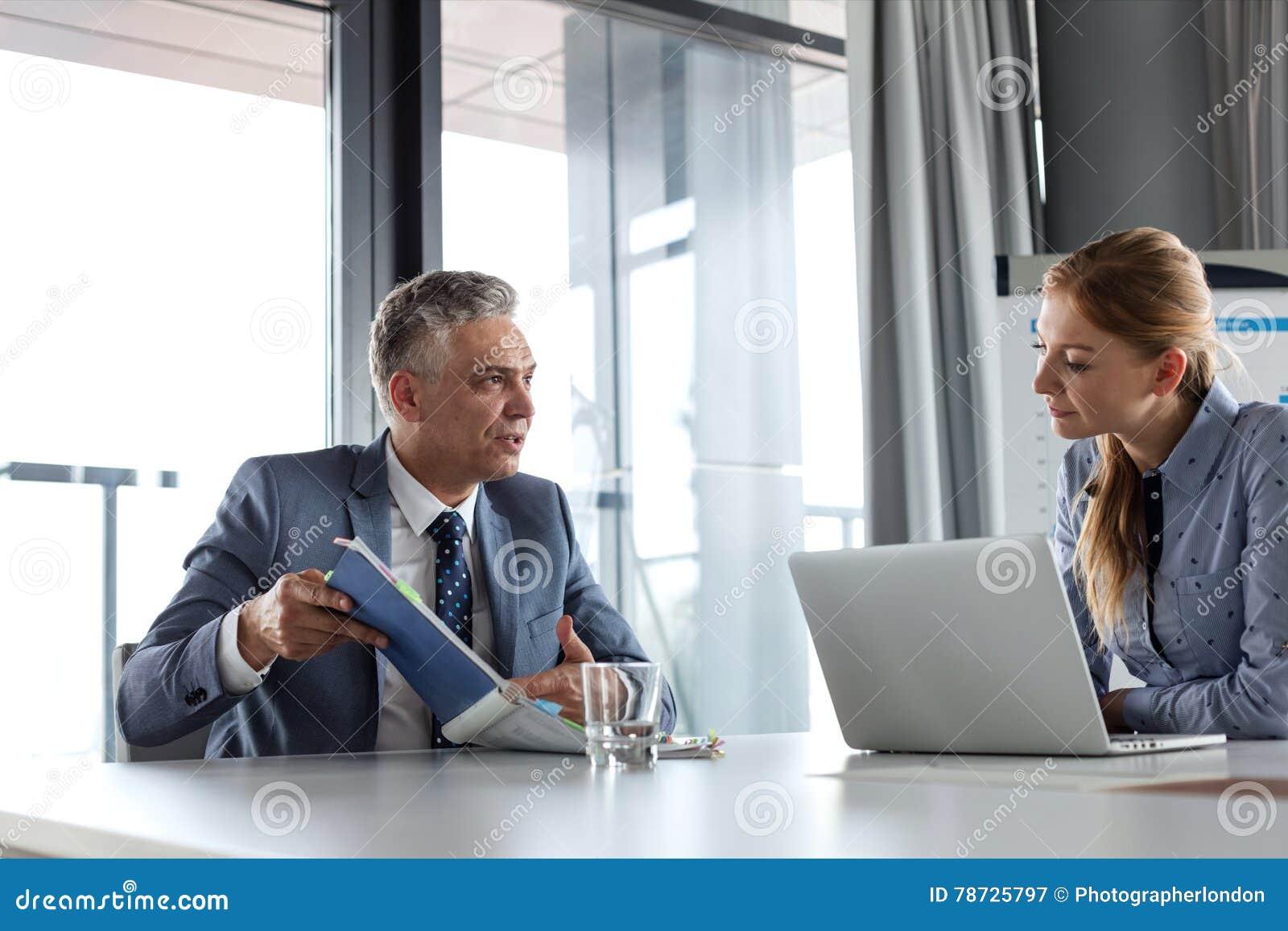 Mogna affärsmanvisningdokument till den kvinnliga kollegan på konferenstabellen