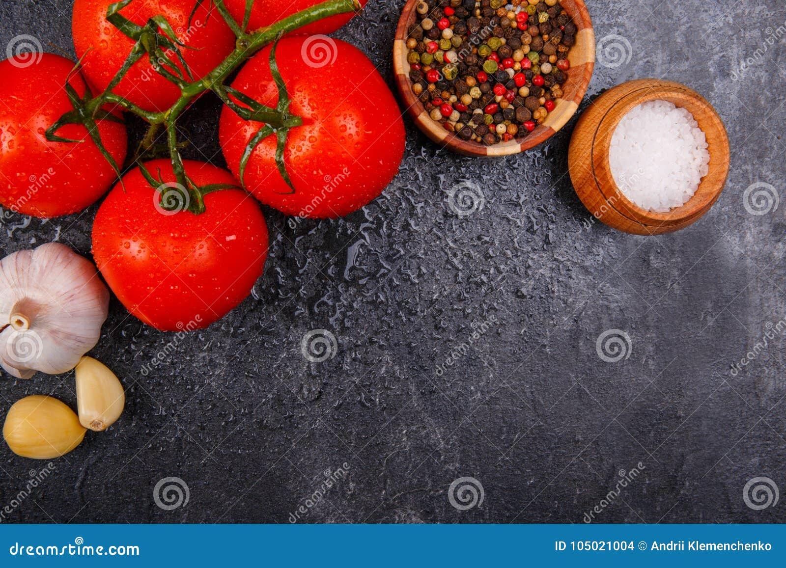 Mogna aptitretande ljusa tomater med pepparkorn, vitlök och saltar på en svart bakgrund, där är rum för text Beskåda