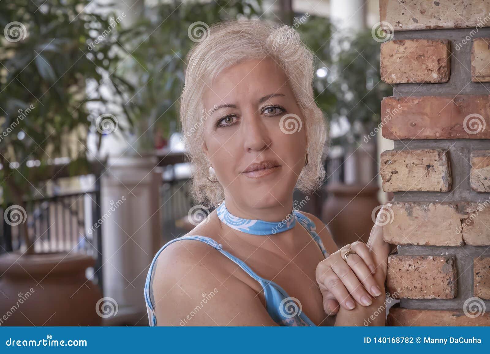 Mogna blonda kvinnor lutar med händer på en tegelstenvägg som ser kameran med ett angenämt leende
