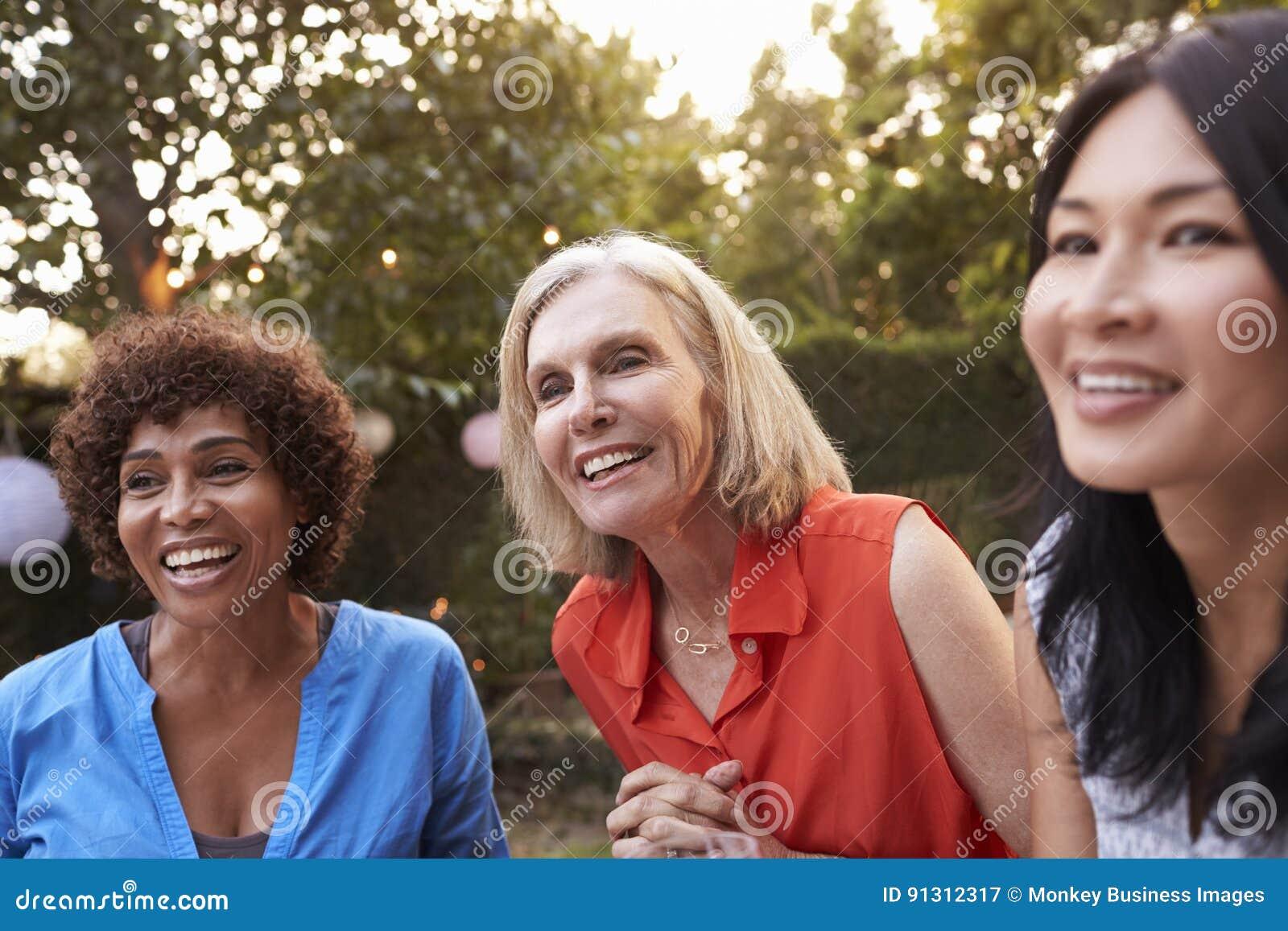Mogna kvinnliga vänner som tillsammans umgås i trädgård