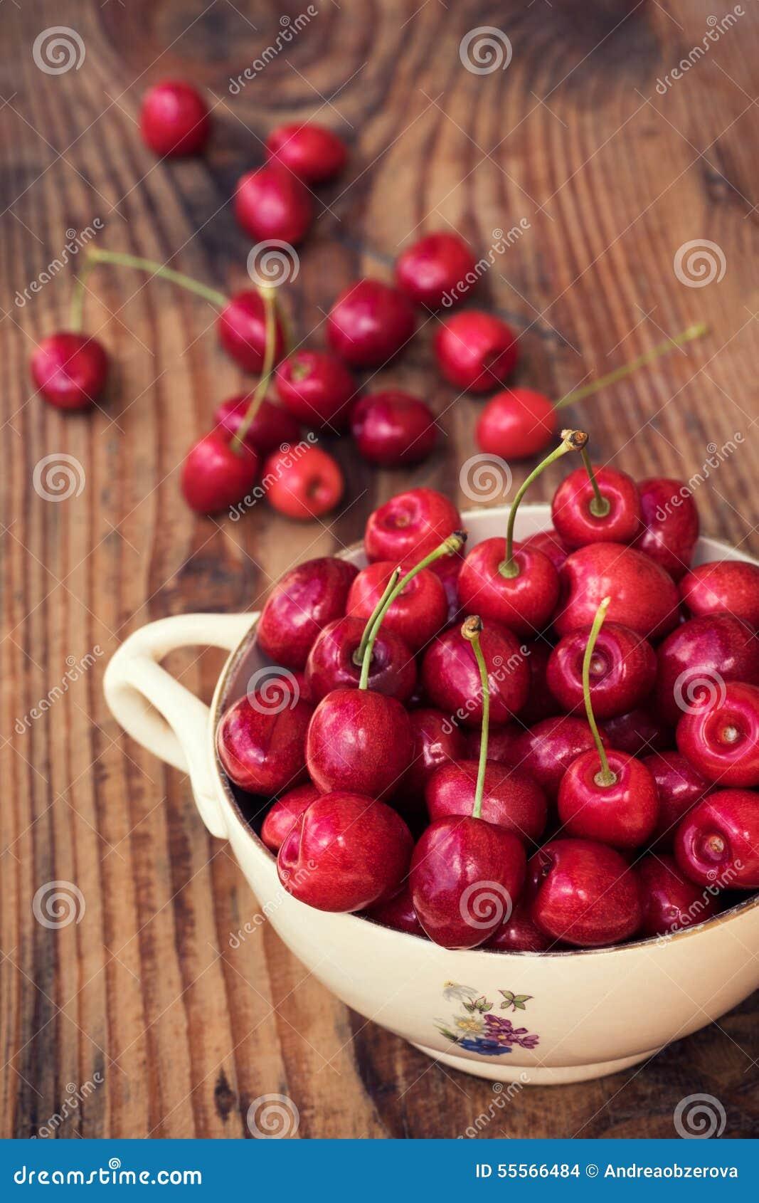 Mogna organiska självodlade körsbär och stenar i en keramisk bunke för tappning