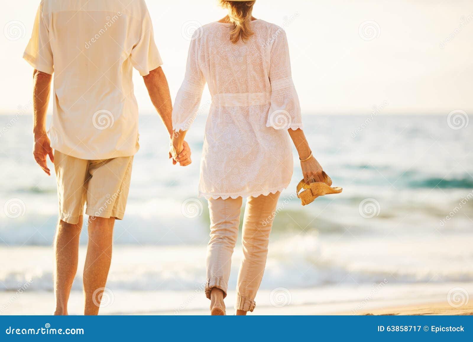 Mogna par som går på stranden på solnedgången