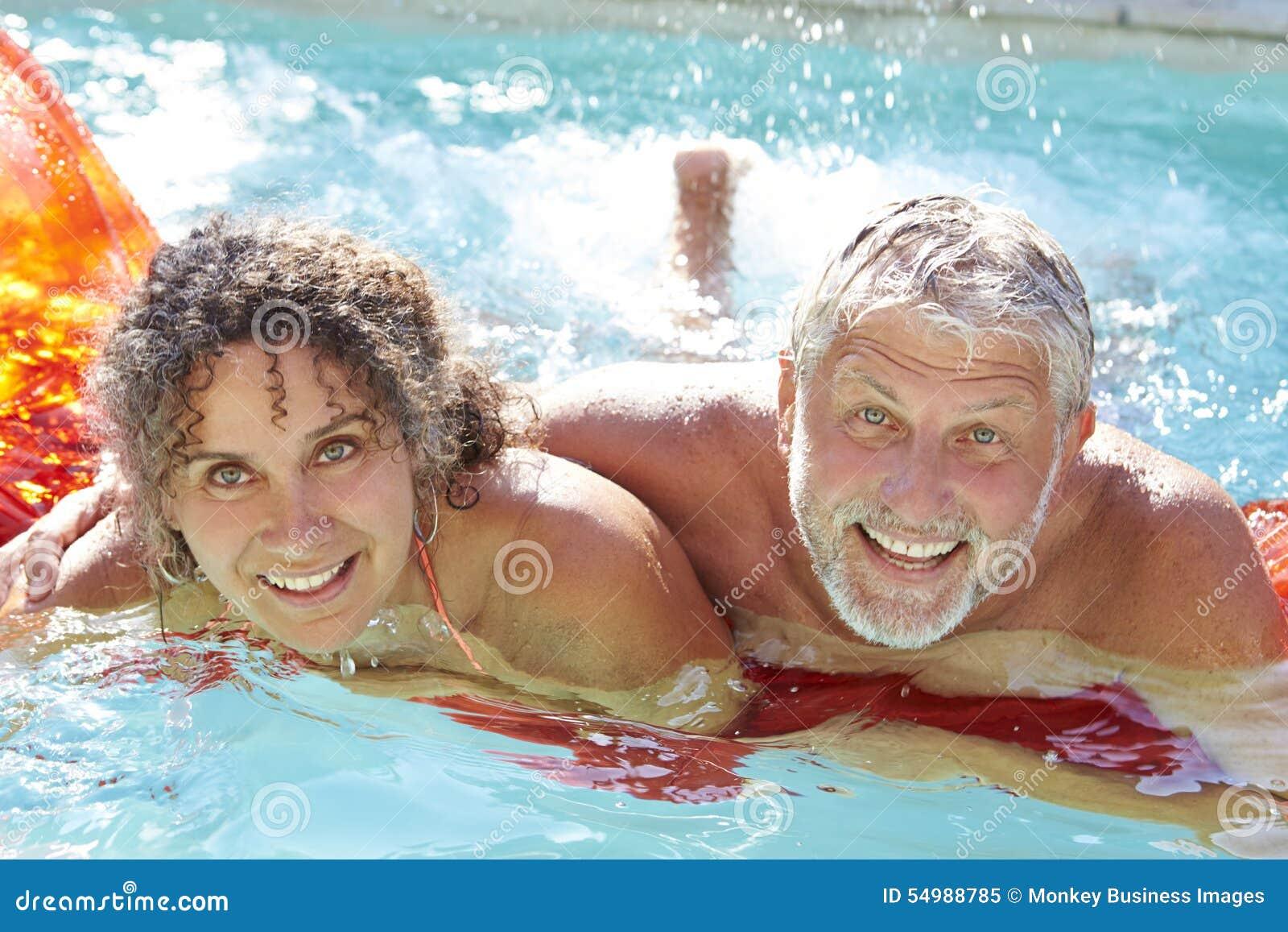 Mogna par som kopplar av på luftmadrass i simbassäng