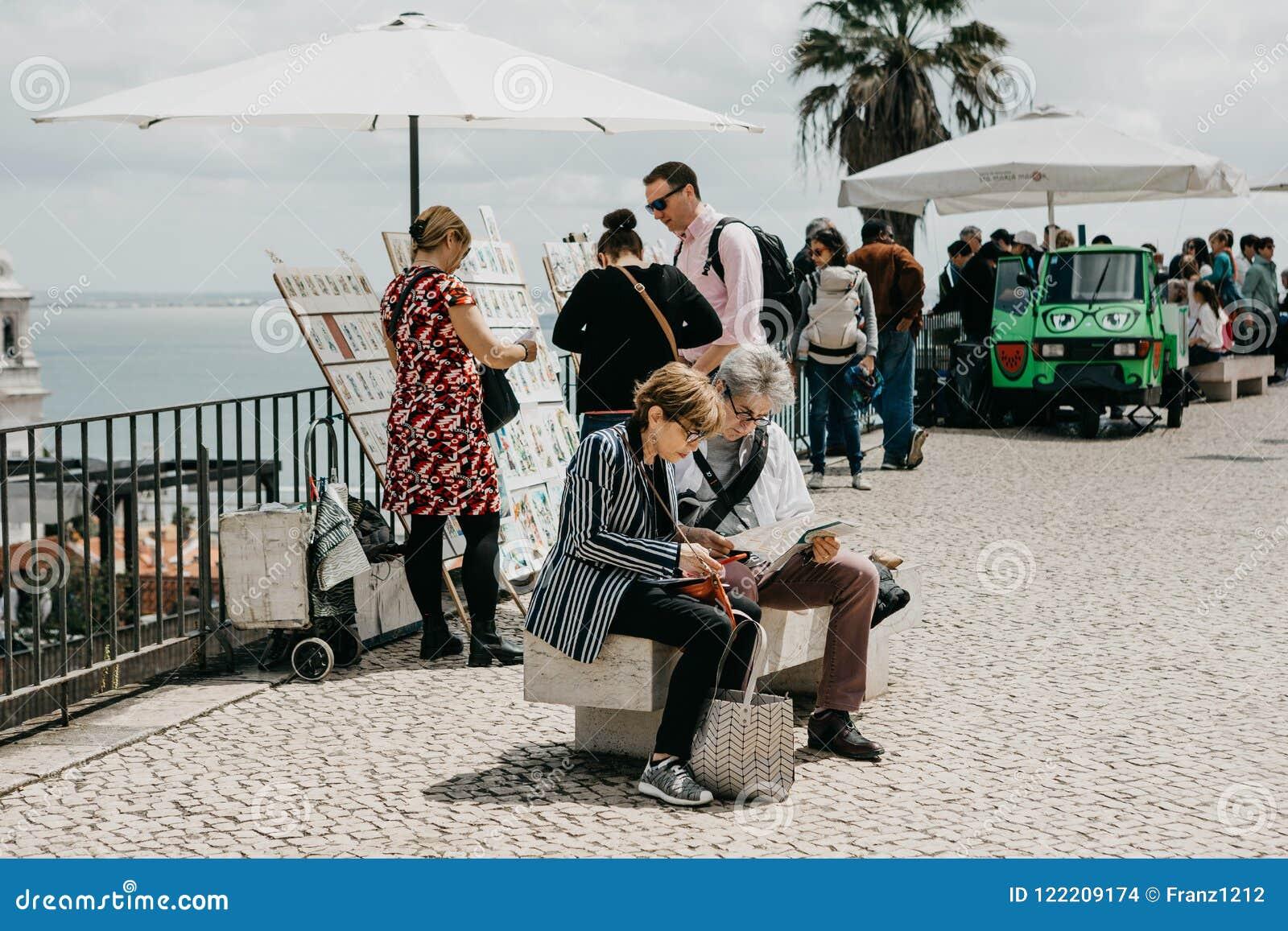 Mogna parsammanträde på en bänk och att se en översikt i Lissabon i Portugal