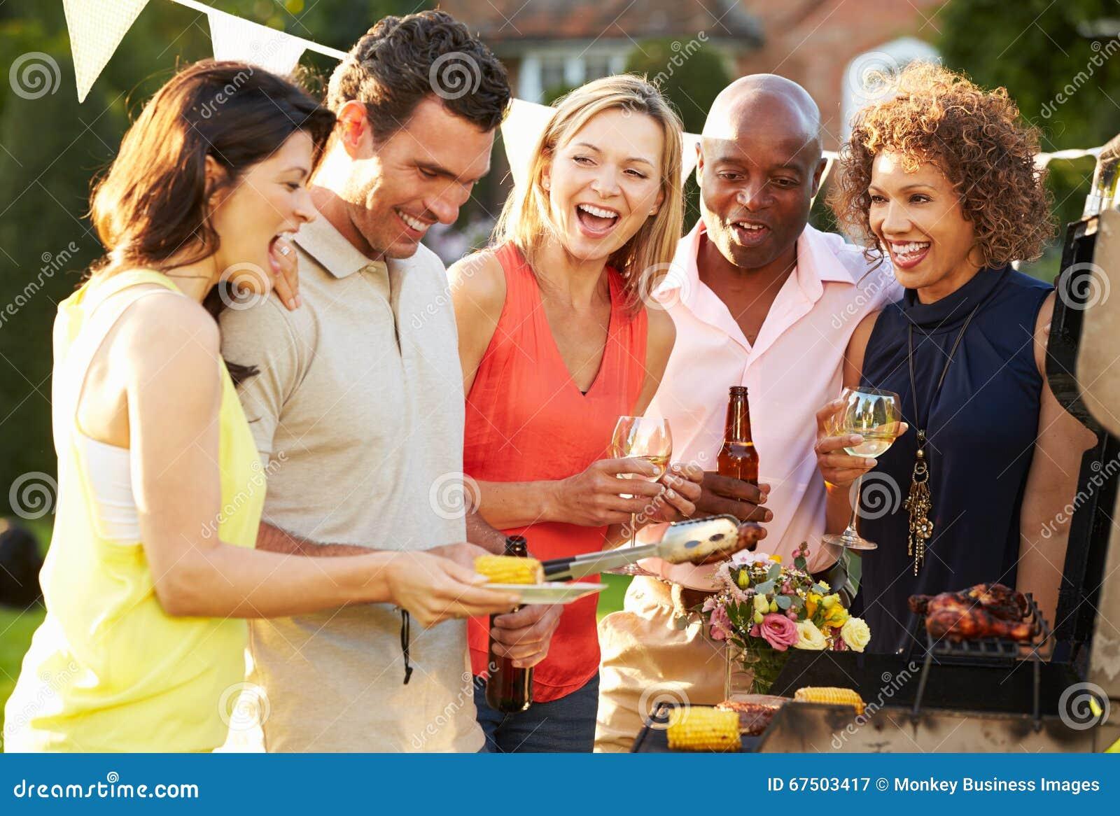 Mogna vänner som tycker om den utomhus- sommargrillfesten i trädgård