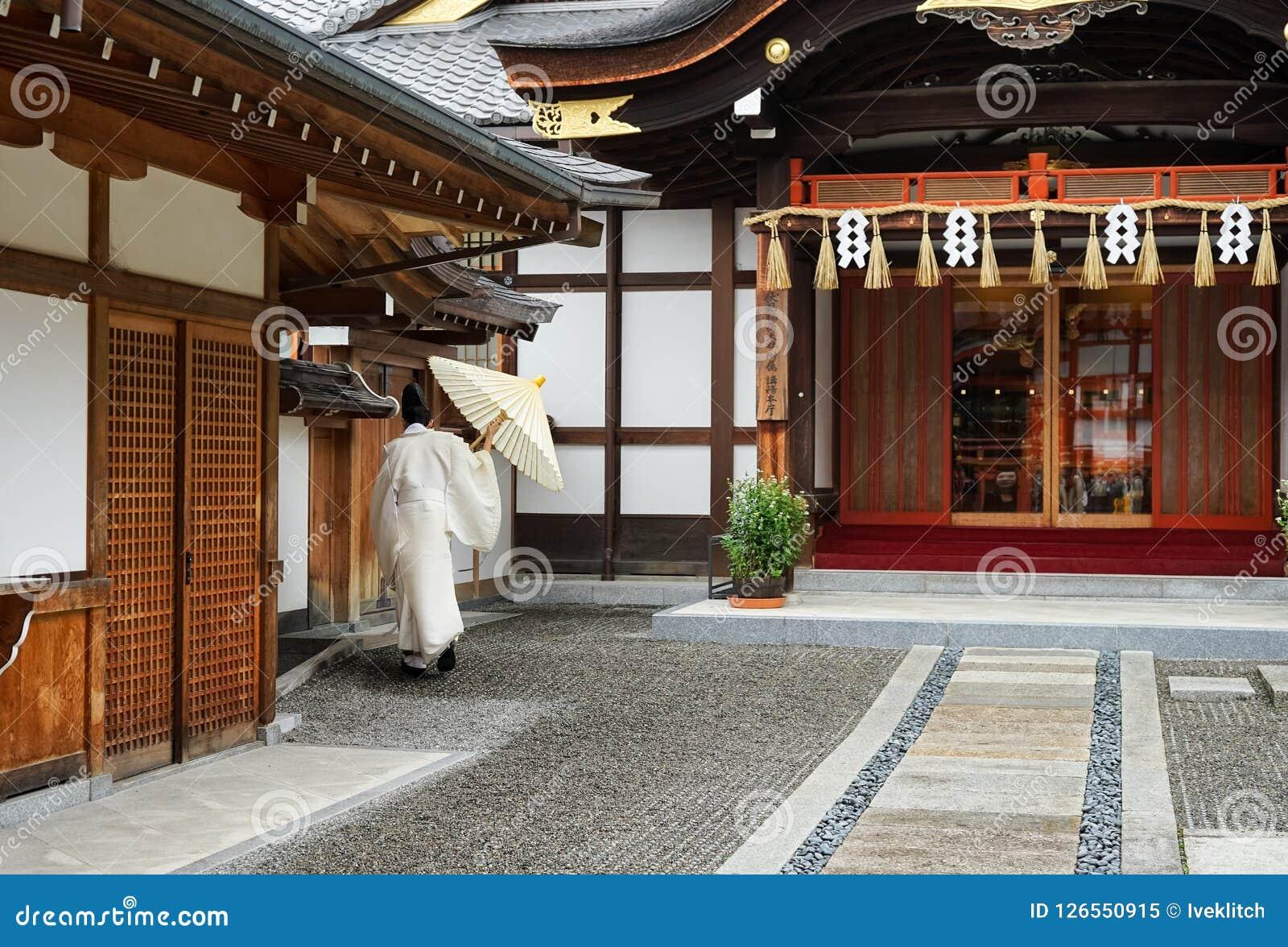 Moine japonais dans la robe blanche par derrière dessus dehors dans le temple Kyoto