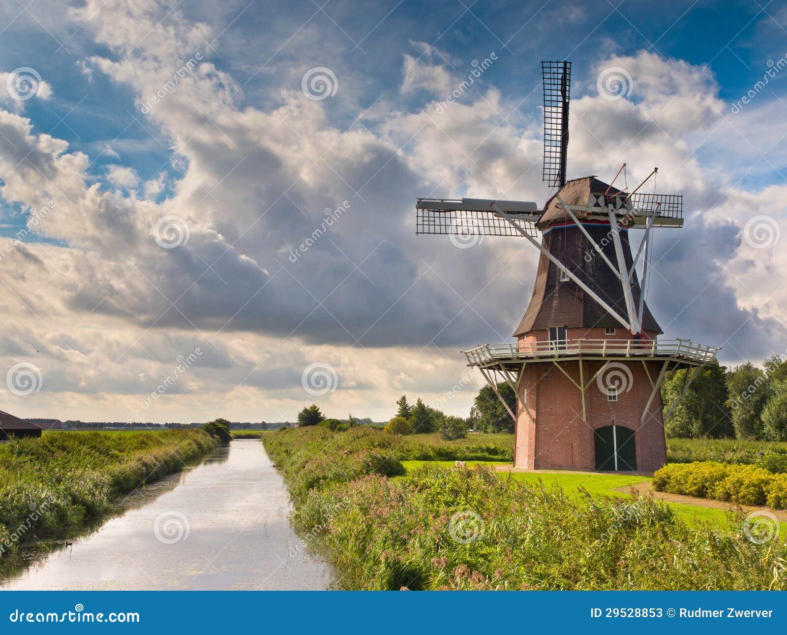 Moinho de vento holandês além de um canal
